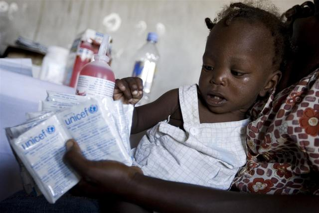 On 23 October, a toddler and her mother receive packets of oral rehydration salts (ORS) at the health centre in Grand Dessalines, a town along the Artibonite River. The river is believed to be contaminated with cholera. The package of ORS bears the UNICEF logo. [#11 IN SEQUENCE OF 12]  By 26 October 2010 in Haiti, an outbreak of cholera had infected 3,342 people, killing at least 259. Cholera is a deadly bacterial infection spread through contaminated food and water; children are the most vulnerable. The outbreak is the countrys biggest medical crisis since the 12 January earthquake. Even before the quake, Haitis access to sanitation was among the worst in the world, a situation that is now greatly exacerbated by ruined infrastructure. While recovery operations made significant progress in providing safe water and sanitation to quake survivors, communicable diseases have remained a persistent threat. The outbreak primarily affects the Artibonite and Central departments, but suspected cases have also been reported in the North and West departments. Five cases have been confirmed in Port-au-Prince, where some 1.3 million people live in dense camps with inadequate sanitation facilities, making them highly vulnerable to a cholera epidemic. In response, Government and humanitarian agencies have stepped up surveillance and prevention measures in the capital. UNICEF and partners are providing medical teams to assist overwhelmed hospitals, and are distributing water purification chemicals, antibiotics, diarrheal disease kits, oral rehydration salts (ORS) and therapeutic foods to affected regions. The Haitis sanitation agency, DINEPA (Direction Nationale de l'Eau Potable et de l'Assainissement), is distributing chlorine tablets and safe water, and is testing water sources for contamination. The Government, together with the World Health Organization (WHO) and other partners, is establishing cholera treatment centres throughout the country, and is launching a public informati