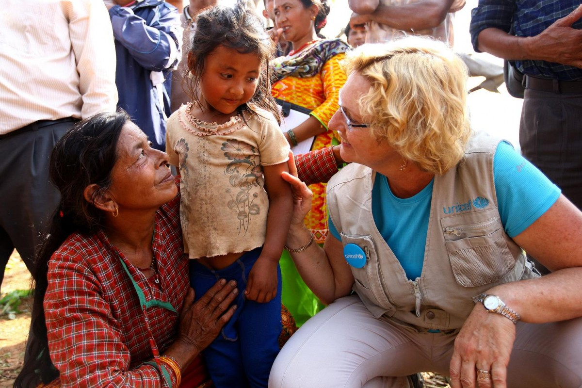 On 1 May, UNICEF Regional Director for South Asia Karin Hulshof speaks with a young girl and her mother in the remote village of Maidi, Dhading District. Other people are gathered around them. Ms. Hulshof's vest as well as a button affixed to it bear the UNICEF logo. In Dhading – which is among the districts severely affected by the earthquake – hygiene kits, water purification tablets and food items have been airdropped to affected populations, and repairs have begun to restore the area's water supply.  On 1 May 2015 in Nepal, search, rescue and relief operations continue in the aftermath of the massive 7.8-magnitude earthquake that hit the country on 25 April. The quake's epicentre was 80 kilometres from Kathmandu, the capital. Over 6,200 people have been killed, and more than 14,300 others have been injured. Over 4.2 million people have been seriously affected, out of which an estimated 1.7 million – 40 per cent – are children below the age of 18 years. Residences, schools and vital infrastructure, including hospitals, have been severely damaged or destroyed, leaving thousands of children and families homeless, vulnerable to disease outbreaks and in urgent need of food, shelter, safe water and sanitation, and health support. Over 3 million people are estimated to be in need of food assistance, with 1.4 million needing priority assistance. As of 30 April, some 24,000 internally displaced people were being hosted in 13 camps in Kathmandu, the capital. Working with the Government and other partners, including fellow United Nations organizations, UNICEF is supporting water, sanitation and hygiene (WASH), health, nutrition, child protection, education and other interventions. In response to the disaster, UNICEF has provided tents, including for hospitals; tarpaulin sheeting; emergency medical kits; vaccines and related supplies; zinc and oral rehydration salts to prevent diarrhoeal disease outbreaks; water purification tablets; hygiene kits and buckets