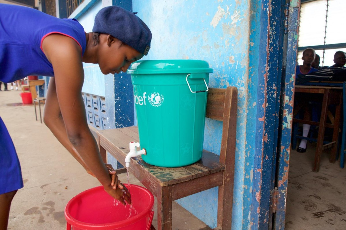 On 14 April, a girl washes her hands with water from a covered bucket with a tap before entering a classroom, at St. Joseph's Secondary School in Freetown, the capital. Hand-washing is part of the strict safety protocols being implemented in all schools across the country, to minimize the risk of Ebola virus disease (EVD) transmission at school. The UNICEF logo is on the bucket.  In March/April 2015 in Sierra Leone, as schools across the country prepare to reopen after an eight month closure due to the Ebola virus disease (EVD) crisis, the Government, UNICEF and partners are working to ensure that children remain safe by reducing as much as possible the risk EVD transmission. Schools – which had remained closed across the country after the July-August break – are scheduled to reopen on 14 April, with some 1.8 million students expected to resume their studies. To support students' return, UNICEF has facilitated the training of 9,000 teachers to implement safety protocols to minimize the risk of transmission at schools, including taking children's temperatures when they arrive at school and making them wash their hands before entering the classroom. UNICEF is also supporting the distribution of hygiene materials and cleaning equipment to prepare school buildings and to reduce the chance of infections; and is providing 24,300 hand-washing stations (about three per school), as well as 1.8 million school kits and psychosocial support for students. UNICEF is also supporting social mobilization activities to raise awareness, and daily government emergency radio education programmes to allow children to continue learning at home during the Ebola crisis, and has distributed some 17,000 solar radios to children in rural communities.