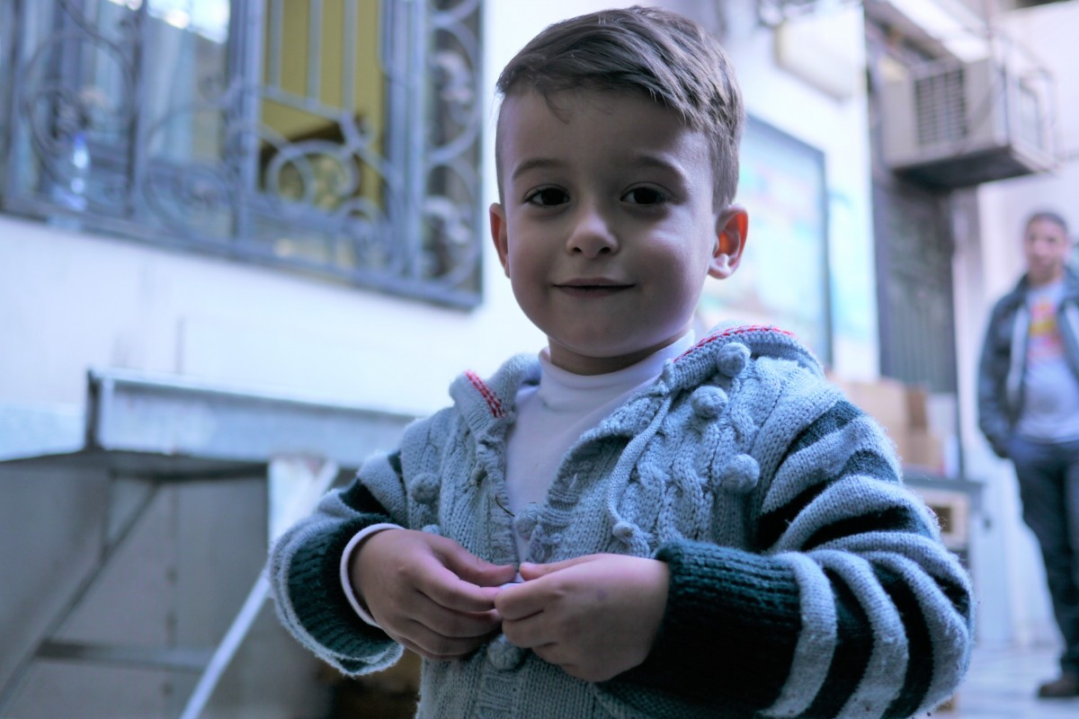 On 9 November 2015, a boy posing for picture at a winter supplies distribution location in Damascus, Syrian Arab Republic.  The boy is waiting for his aunt as she picks up a winter kit for him.  UNICEF aims to reach one million children with winter clothes and supplies during the 2015/16 winter season.  Cold weather is fast approaching and is likely to further exacerbate the situation for children who have already been affected by nearly five years of conflict. Winter conditionscan be harsh especially in remote and hard to reach areas. Last year, temperatures dived to -13 degrees centigrade in many parts of the country. UNICEF is distributing age and gender appropriate winter clothing kits and thermal blankets to families in need.