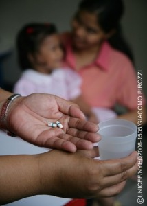 A health worker holds ARV medications and a glass of water in her hands at a child care centre in Tondo, a neighbourhood of Manila, the capital. Behind her, an HIV-positive child sits with a caregiver. The centre is run by Precious Jewels Ministry, a UNICEF-assisted centre NGO that offers medical assistance, educational activities and counselling for AIDS-affected children, as well as community outreach to raise awareness of HIV/AIDS and combat the stigma associated with the disease.  In 2006 in the Philippines, HIV transmission is hidden and growing. While official statistics cite fewer than 10,000 HIV cases nationwide, high-risk behaviours, especially among adolescents, are on the rise. Those at highest risk are children in depressed, urban areas, those who live or work in the streets and those involved in the sex industry. Many have limited access to basic services like education, community support and health care. And a strong culture of stigma, denial and silence has prevented an open discussion of HIV/AIDS, sexuality and adolescent reproductive health. Other factors impeding prevention and care services include limited knowledge and skills among health-care workers; rapid turnover and migration of staff; and disruption of health systems due to emergencies and conflict. On Mindanao Island, a decades-long conflict between Christians and Muslims has killed, injured or displaced thousands of children, and left others vulnerable to abduction, trafficking and abuse. Working with government, NGO and other partners, UNICEF supports peer counselling and prevention awareness training for adolescents; expanded voluntary counselling and testing services; and treatment, care and support services for children infected with HIV/AIDS. UNICEF also supports child protection, peace building and the delivery of social services in conflict areas.