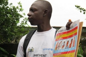 In August 2014 in Sierra Leone, an outreach worker holds a poster bearing information on the symptoms of Ebola virus disease (EVD) and best practices to help prevent its spread, in Freetown, the capital. The posters are among those UNICEF has produced for distribution as part of social mobilization efforts. The worker's T-shirt bears the UNICEF logo. As of 4 August, a total of 1,711 cases, including 932 deaths, had been attributed to EVD in the four West African countries of Guinea, Liberia, Nigeria and Sierra Leone. Sierra Leone has borne 691 of these cases (576 confirmed, 49 probable and 66 suspected), including 286 deaths.