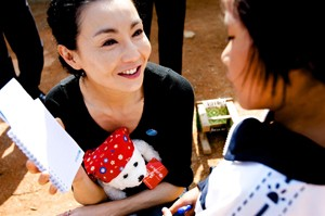 UNICEF Goodwill Ambassador Maggie Cheung gives a teddy bear and notebook to a girl who is HIV-positive, in Ruili City, Yunnan Province. The teddy bear and notebook display the UNICEF logo. In April 2010 in China, acclaimed international actress and newly appointed UNICEF Goodwill Ambassador (China) Maggie Cheung visited children and women affected by HIV/AIDS in Ruili City, in the south-western province of Yunnan. Although China has relatively low rates of HIV infection, the risk of transmission is significantly higher in parts of Yunnan Province, which borders major opium producing regions in neighbouring countries. HIV prevalence is 0.1 per cent nationally, but rises to 20 per cent among intravenous drug users in Yunnan. The disease remains highly stigmatized and poorly understood by much of the population, factors that could accelerate the spread of the epidemic, particularly among the rural poor, migrants, sex workers and injecting drug users. On 29 April, Ms. Cheung was appointed a UNICEF Goodwill Ambassador to advocate on behalf of vulnerable children, including those affected by HIV/AIDS and disability. Her visit to Yunnan aimed to raise awareness of HIV/AIDS and to mitigate stigma associated with the disease. By the end of 2007, an estimated 700,000 Chinese were HIV-positive.