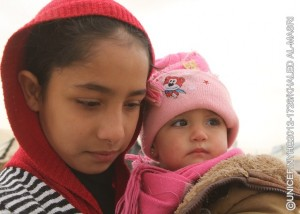 Both bundled in winter clothing, a girl holds an infant, in Za'atari, a camp for Syrian refugees on the outskirts of Mafraq, capital of the northern Mafraq Governorate. The camp is currently hosting 66,394 people. On 20 December 2012 in Jordan, worsening winter conditions continue to threaten Syrian refugee children and their families. To date, 106,724 refugees from Syria's still escalating war have registered in Jordan with the United Nations High Commission for Refugees; an additional 41,868 are awaiting registration. Syrians have also fled to neighbouring Iraq, Lebanon and Turkey, and as far away as Egypt, bringing the total number of registered refugees to 450,191. Inside Syria, some 2.5 million people have been affected by the conflict, of which 1.1 million are children. In Jordan, where the number of refugees continues to increase, UNICEF and partners are supporting the ongoing provision of winter supplies. In the Za'atari camp as well as in the King Abdullah Park and Cyber City transit sites for refugees, some 3,000 winter clothing kits for infants under age 1 are being distributed. Over 3,100 additional kits are also being procured for new arrivals during the winter. Additional support includes the ongoing installation of gas boilers to provide hot water in Za'atari's 90 existing water, sanitation and hygiene units and the construction of 192 fully winterized units in new areas of the camp. UNICEF also supports initiatives in health, nutrition, water, sanitation and hygiene, education and child protection, including the provision of child-friendly spaces and psychosocial assistance for children traumatized by their experiences in relation to the conflict. Working with diverse governments, other United Nations organizations and local and international NGOs, UNICEF continues to respond to the needs of affected children in all host countries and inside Syria. To continue these responses over the first six months of 2013, UNICEF requires US$180 million.