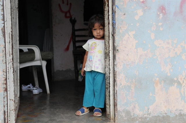 A small girl stands inside the doorway of her home in Moravia, a poor neighbourhood in Medellín, capital of Antioquia Department.