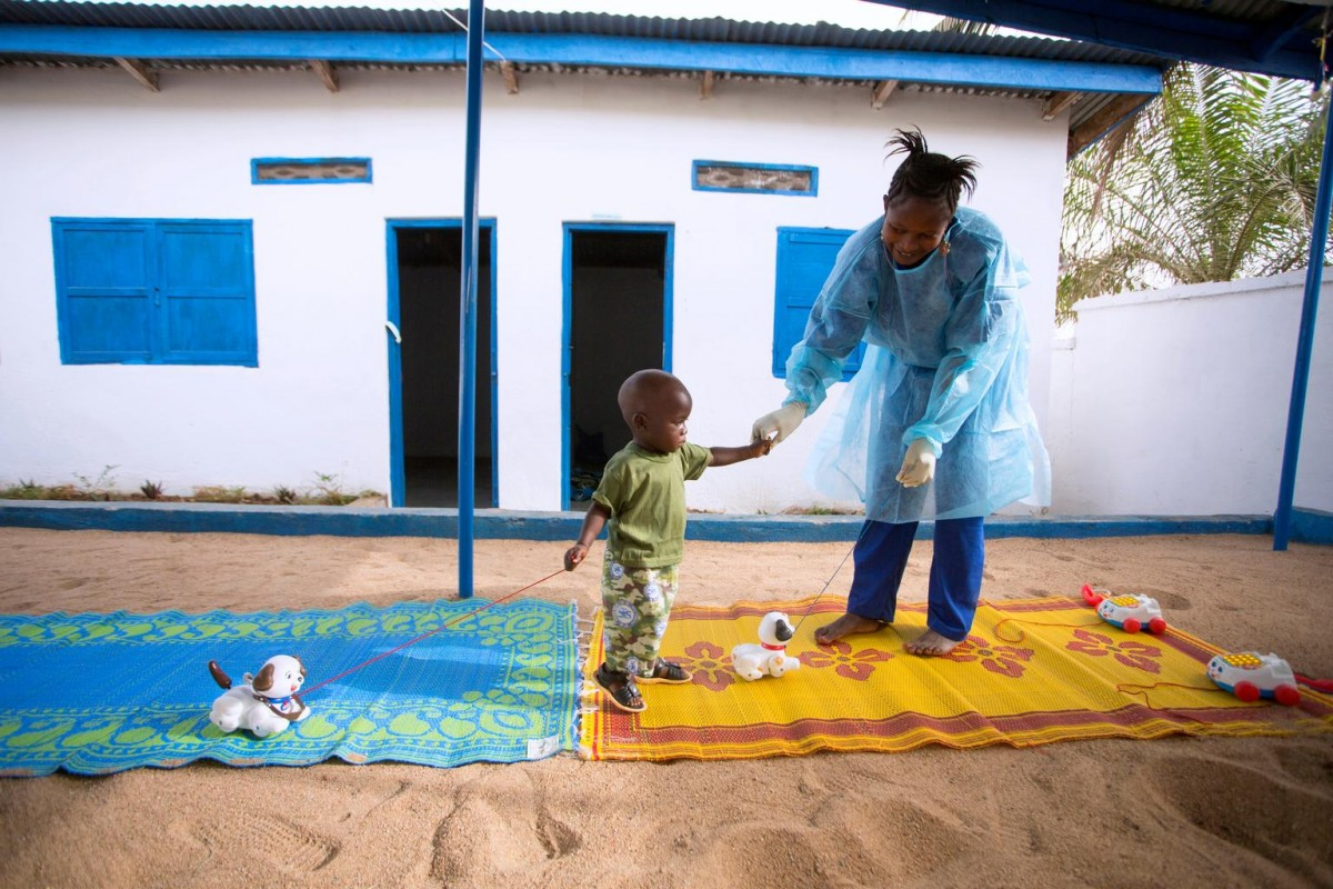 "On 11 January in Guinea, 19 month old Tamba Manzare and caregiver Rose Komano play outdoors at a UNICEF-supported nursery in Guéckédou Prefecture, Nzérékoré Region. Tamba, whose mother died from Ebola virus disease (EVD), is being quarantined for 21 days – the virus's maximum incubation period. Ms. Komano, who is wearing some protective clothing, is an Ebola survivor. ""I want to ask all the organizations [that] are helping us not to forget these children,"" she said. ""Because if they are forgotten, tomorrow they could become sick. So please don't forget them."" UNICEF and partners continue to provide vital support, including efforts to raise awareness of the disease and effect behavioural changes to help halt its spread."