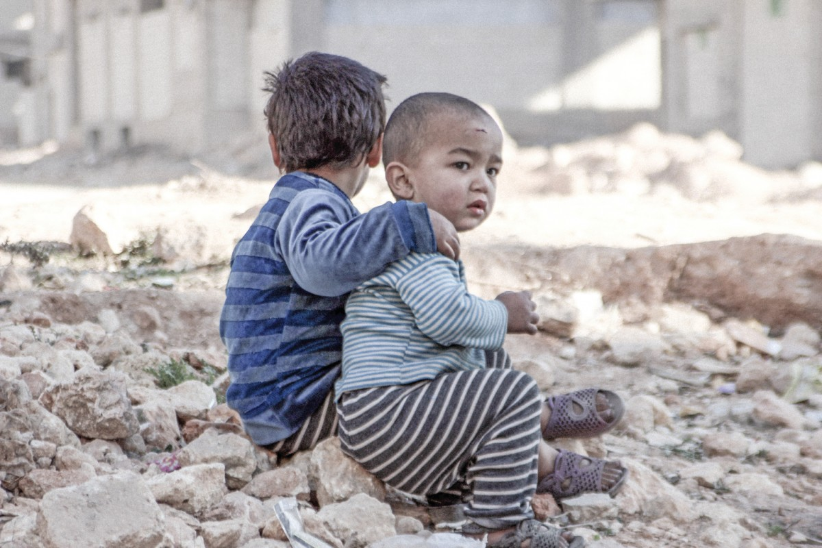 On 25 December 2015 in Aleppo in the Syrian Arab Republic, Esraa, 4, and her brother Waleed, 3, sit on the ground near a shelter for internally displaced persons.