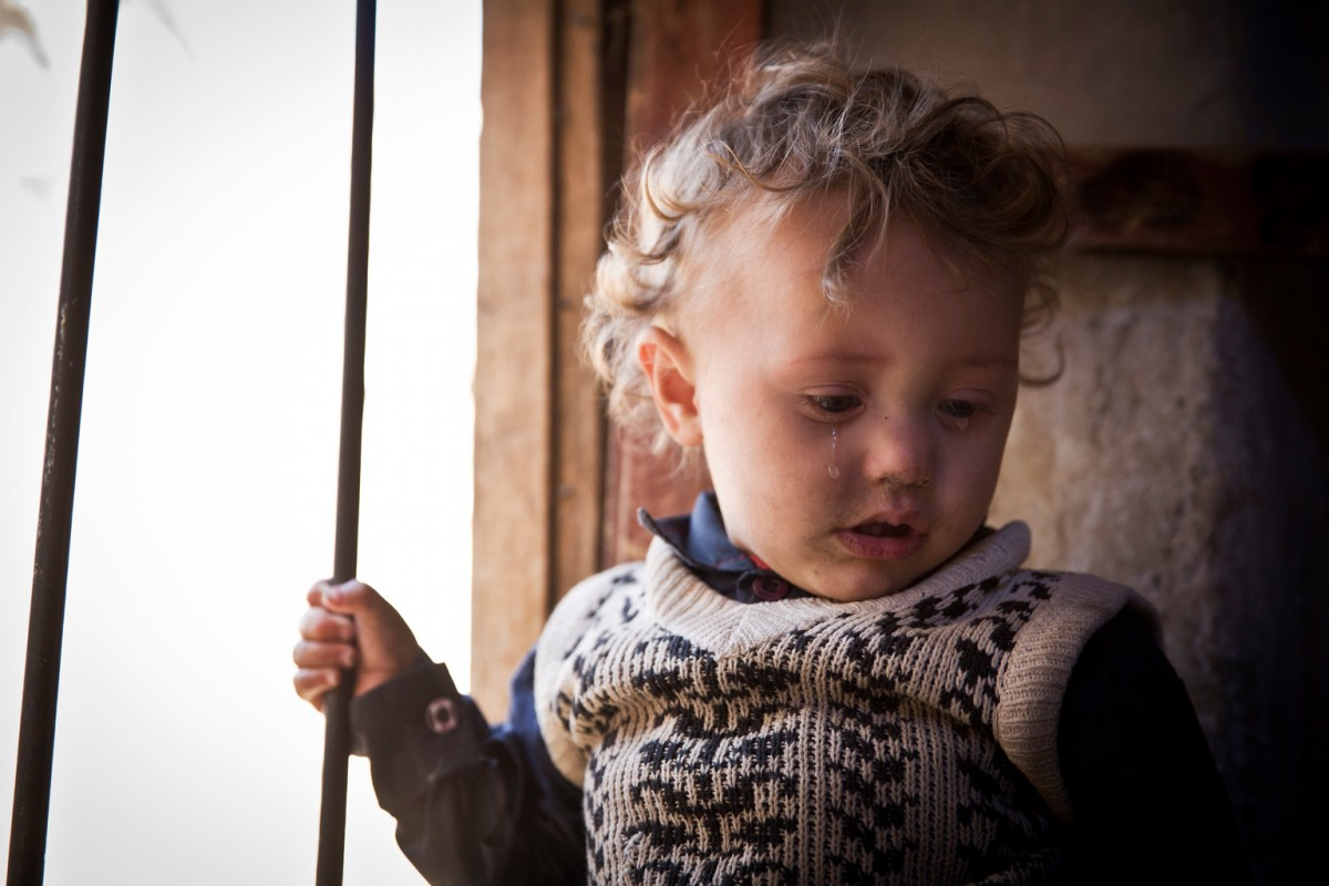 """A Muhamasheen child is seen inside her house in the Muhamasheen area of Mathbah, in Sana'a, Yemen, November 2, 2015.  Yemen is suffering and its people are facing some of the worst moments in human history. This extreme hardship is affecting the most vulnerable of the Yemeni society. The absence of any coping mechanism for such vulnerable households is further pushing millions of Yemenis into extreme poverty.  This tragic turn is exacerbated by the suspension of the Social Welfare Fund (SWF) since March 2015, which has been the key """"public social protection"""" buffer, covering almost 7.9 million Yemeni lives. Out of these poverty stricken millions, are an even further marginalized group known as the Muhamasheen. They survive on the fringes of society, living in slums and peripheral areas of urban, semi-urban, and rural Yemen. But the recent conflict has not been the sole cause of their misery. This community has been neglected for a fairly long time. With limited access to basic social services, their social indicators are far worse than that of any average citizen. And now the conflict has worsened their condition to a question of survival.  In December 2015, a recently concluded Muhamasheen Mapping Survey (MMS) has indicated that only 25 % of all Muhamasheen have durable housing, compared to 54 % of the general population; only 9% have access to piped water compared to the national figure of 29%; almost 22 % have to survive out in the cold, living in tents and makeshift hutments made of tin and cardboard; the majority 59% live in dilapidated and deserted houses. The statistics for the affected children is a lot worse: almost 52% of their children between ages 10 -14 age group, cannot read and write, compared to 17% at the national level and 40% of the poorest quintile; for the age group of over 15 years, 80% cannot read and write, compared to 40% of the same group at the national level, and 68% of poorest quintile.   The Social Welfare Fund exclusion error margin"""