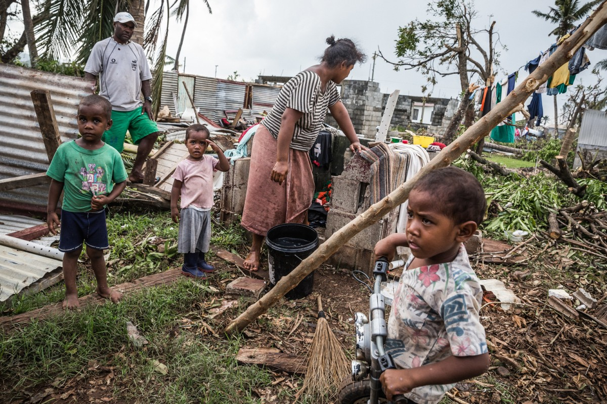 Lasaro Vota, his wife and children (from left to right) Lasaro Junior (5), Seremaia (3) and a neighbours' son Manoa (3) are cleaning the debris of their home in Navuavua village in Ra Province. Lasaro kept safe during the night by taking shelter inside a deep freezer.