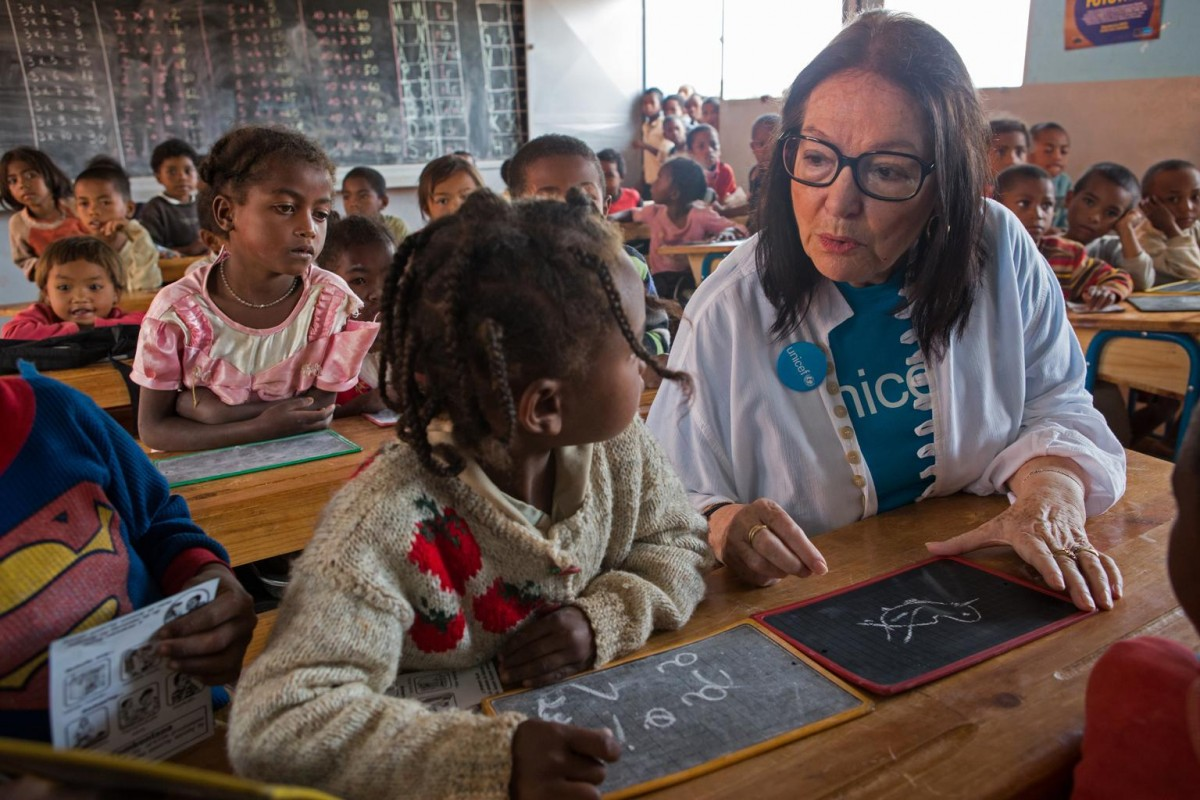 On 26 February, (foreground, right) UNICEF Goodwill Ambassador Nana Mouskouri chats with 7-year-old student Fifaliana Raholinirina in a class at a public primary school in Ampangabe Village in Analamanga Region.  From 24 to 28 February 2015, internationally acclaimed singer, humanitarian and UNICEF Goodwill Ambassador Nana Mouskouri visited Madagascar to review UNICEF-supported programmes and to draw added attention to the considerable challenges and constraints faced by the country's vulnerable children and families. Madagascar is slowly emerging from a protracted and debilitating political crisis and the ensuing economic decline. The country remains one of the world's poorest: 91 per cent of the population live on less than US $2.00 a day, and many of the poorest are children – who have been hardest hit in the crisis and live in extreme poverty. The crisis also resulted in a decrease in public investment in social sectors, weakening further the delivery of basic social services, as well as access to, and use of, these vital services. The health, education, and water, sanitation and hygiene (WASH) sectors have seen significant declines. Madagascar is ranked as the fourth-worst country in the world in terms of access to safe drinking water, and eight from last in access to sanitation. Only half of the overall population and 35 per cent of the rural population have access to improved water sources, with 38 per cent of people in rural areas relying on surface water for drinking; and just 14 per cent of the population has access to improved sanitation facilities. Nearly half (47 per cent) of all children under age 5 are stunted – the fourth-highest rate in the world; and maternal mortality remains very high, at 500 per 100,000 live births. The country is also no longer on track to achieve universal primary-school education. The net primary enrolment rate has decreased (from 83 per cent in 2005 to 69 per cent in 2012), and about 1.5 million school-age children