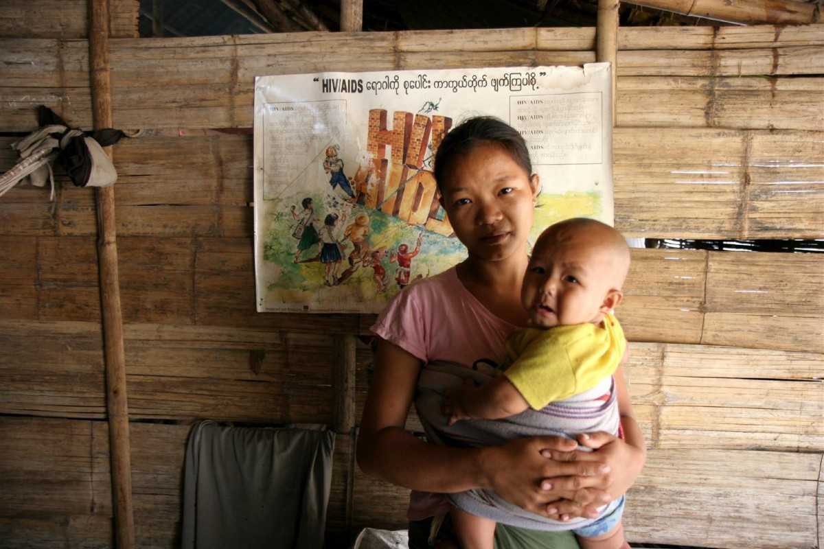 A mother holds her child in front of an HIV/AIDS prevention poster at the Baan Mai Nai Soi refugee camp in Mae Hong Son Province near the Myanmar border.  In 2006 in Thailand, the recent flood of refugees from Myanmar is taxing already overcrowded camps along the Thai-Myanmar border. To date, approximately 140,000 Myanmar refugees, nearly 40 per cent of whom are children, live in the region's nine camps. Many refugees arrive weakened by illnesses such as malaria. The dangerous journey can take months to complete. At the Baan Mai Nai Soi camp in Mae Hong Son Province, limited space forces families to live together in small, temporary structures. Some families have lived in the camp for over 15 years. Opportunities for employment are rare and those who do find work frequently leave their children unsupervised, making them vulnerable to sexual abuse, human trafficking and abduction into the armed groups of political factions located near the camps. Basic services and education are limited. The UNICEF-supported NGO, Catholic Office for Emergency Relief and Refugees (COEER) is working to establish protection services and centres in the camps where children can access psychosocial counselling and report abuse. UNICEF is also advocating for birth registration and surveys to locate out-of-school children, as well as providing health and hygiene kits to new mothers.