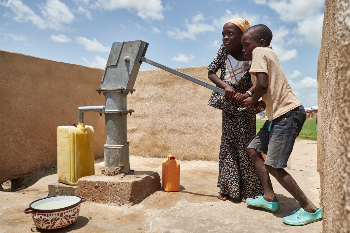 Mataram (yellow veil) and a boy pump water from a water hole installed by UNICEF in a displaced people camp in Garin Wazam, Niger on August 10, 2016. Garin Wazam is located 55km east of Diffa town and currently host an estimated 22,800 individuals, refugees, internally displaced and host community according to the authorities of Niger. Most of them are Peul, Boudouma and Haoussa and come from Bosso, Yebi and Toumour, having arrived end of May, beginning of June 2016 after Boko Haram attacks. Since July 22th, Garin Wazam now has 6 new boreholes constructed by ACTED with UNICEF support. Before that, the water supply was made possible thanks to water trucking only.   Boko Haram attacks have caused a population displacement and security crisis in the Diffa region. Today, Diffa hosts an estimated 300,000 displaced people (including Nigerian refugees, Nigerien returnees from Nigeria and IDPs), many settled along the RN1, the main road crossing the region. This number includes an estimated 69,000 newly displaced people as a result of the May and June 2016 attacks perpetrated by Boko Haram in Bosso, Yebi and Kablewa. The newly displaced settled on existing sites, putting an enormous pressure on the temporary health facilities in place on the various RN1 sites.UNICEF works to increase access to safe water through the construction/rehabilitation/improvement of water points, installation of emergency water supply devices and water trucking. The agency also promote adequate hygiene practices, distribute water purification products and soap and collaborate with partners to increase access to sanitation facilities in the sites for displaced people and strengthen maintenance and management of water points with implementation and training of committees.