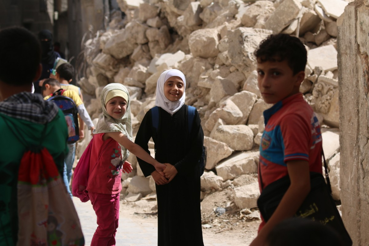 "On 21 September 2016 in eastern Aleppo in the Syrian Arab Republic, Judy (white head scarf), 9, and her schoolmates return from the first day of school passing the rubble of nearby houses.  ""I go to school every day, except for the times when I hear the planes,"" Judy explains.  ""I want the road to reopen so I can go see my brother who lives in another city and just got married. I haven't even met his wife yet,"" says Judy.  Instead, the road remained closed due to heavy bombardment and shelling. In Judy's neighborhood, electricity is largely unavailable as there is a fuel shortage.    One in four schools are not functioning in the Syrian Arab Republic because they have been damaged, destroyed, or serve as shelters for displaced families or are in use for military purposes.  Over two million children across the country are not able to go back to learning, while another 400,000 children are at risk of dropping out, due to heavy violence, lack of safe learning environments and displacement.  More than 52,000 teachers have left their jobs.  Two decades of investment in learning has been wiped out, as some children have lost up five years of their education, while others have never been to school.    UNICEF is supporting more than 1,200 dedicated young volunteers to conduct a door-to-door campaign to map the numbers and situations of out-of-school children, while reaching out to parents with information about the simplified school enrollment processes and the right to have an education.  Also recently launched is a back-to-learning campaign that aims to reach 2.5 million children in the country, including 154,000 living in besieged and hard-to-reach areas. UNICEF will be providing educational materials, school bags and stationery.  A social mobilization campaign encourages parents to send their children to school or benefit from alternative learning opportunities where schools are no longer functioning.  As part of that campaign, social media, radio and televi"