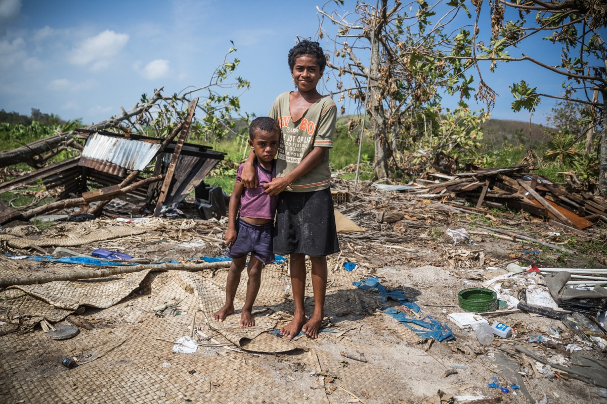 """On 25 February 2016,  Adi (13) and her 4-year-old brother Waisake, outside their home destroyed by destroyed by Tropical Cyclone Winston in  Yaqeta village, Yasawa island group.  Add says: """"I was with my family in a house. Then I saw our house starting to collapse. I grabbed my brother Waisake and we run. I was so scared. We run from house to house three times. Now I am heartbroken to see the house where I was born and raised in, in pieces"""".  Category 5 Tropical Cyclone Winston made landfall in Fiji on Saturday 20 February 2016, continuing its path of destruction into Sunday 21 February. A state of natural disaster and a nationwide curfew had been declared by the Government of Fiji earlier in the evening. In the wake of Cyclone Winston, UNICEF's main concern is for children, pregnant women and breastfeeding mothers across Fiji. Little is yet known about the status of communities living on the outer islands of Fiji that were directly under the eye of Tropical Cyclone Winston- as communications remain down for many. The Fijian Government is rapidly working to assess the overall situation in order to pinpoint the critical needs. The Fijian Government has declared a state of natural disaster for the next 30 days and has initiated the clean-up process by clearing the huge amounts of debris scattered everywhere. UNICEF staff members are standing by to assist as required."""