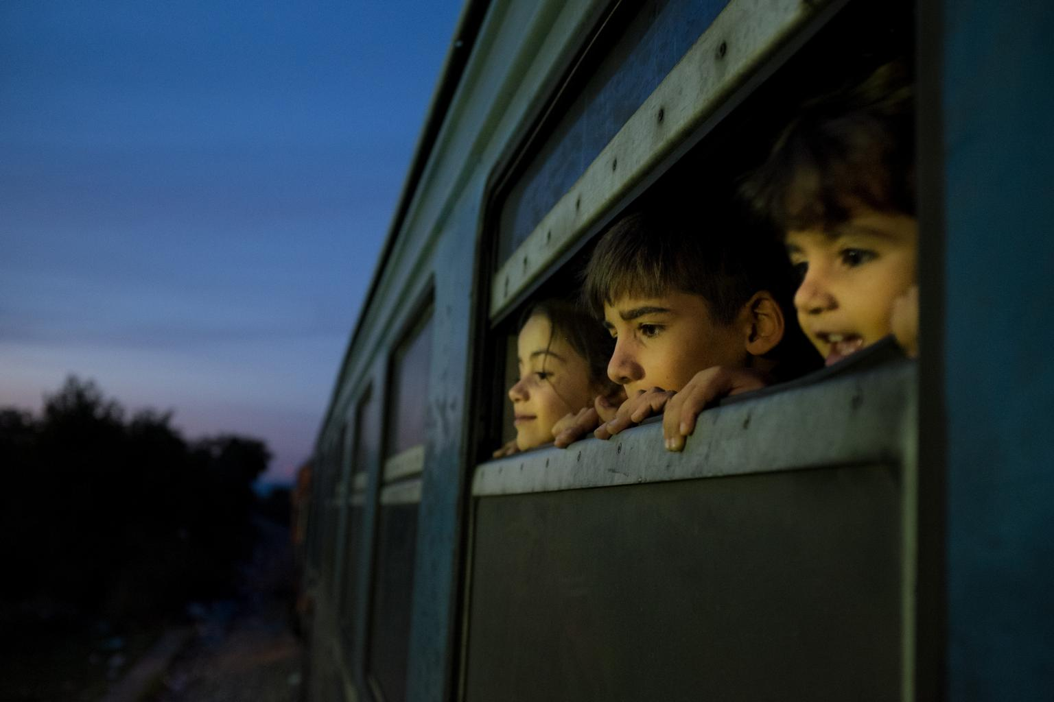 On 2 October 2015 in the former Yugoslav Republic of Macedonia, three children look out of the window of a train as refugees primarily from the Syrian Arab Republic, Afghanistan and Iraq board the train at a reception center for refugees and migrants, in Gevgelija. From here refugees board a special train that takes them Tabanovce close to the border with Serbia.