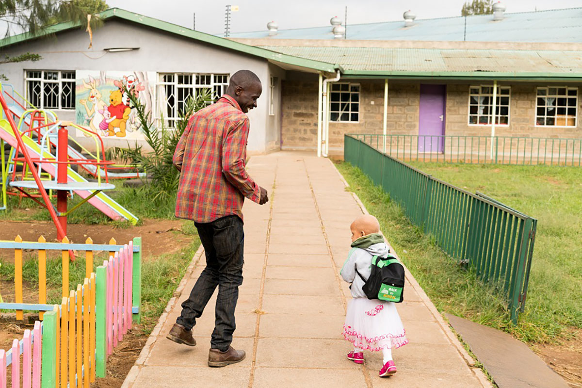 ©UNICEF/Ohanesian Erick Ogutu, 29, runs to class with his daughter Octaviah Achieng, 2, at the Little Rock Early Childhood Development Centre in Nairobi, Kenya.