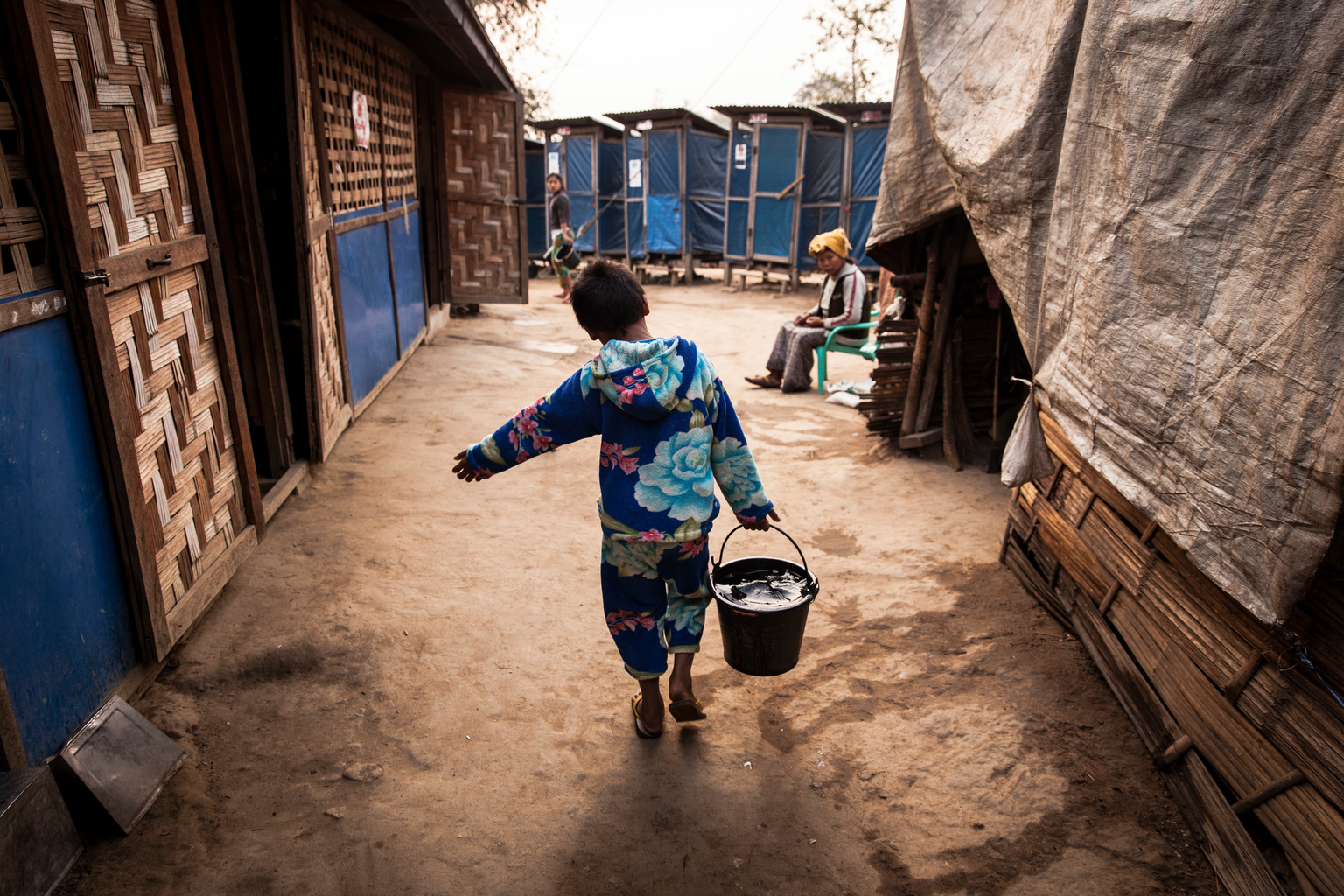 Aung Din, 12, displaced from Mung Ding Pa, collects water every morning for his household at the Phan Khar Kone IDP camp in Bhamo city, Kachin State, Myanmar, Wednesday 29 March 2017. Aung Din lives with his grandmother, mother and sister in the camp - his father was killed in a blast, most likely from a landmine while herding cattle, when fighting erupted between Kachin Independence Army (KIA) and the Myanmar Army in 2013. In 2017, working with the Government of Myanmar, UNICEF will strive to meet the basic needs of the most vulnerable internally displaced children. Myanmar is experiencing three protracted humanitarian crises, each with its own set of complex underlying factors. In Rakhine State, inter-communal violence that erupted in 2012 continues to plague 120,000 internally displaced people spread across 40 camps or informal sites, as well as host communities. Eighty per cent of the displaced are women and children. In Kachin State, armed conflict that reignited in 2011 continues to impact communities caught in the crossfire between an ethnic armed group and the Myanmar army. Nearly 87,000 people remain displaced as a result, including 40 per cent who are in areas outside of government control. An additional 11,000 people remain displaced in northern Shan State, where a similar conflict broke out in 2011. Compounding the protracted crises are issues related to religious and/or ethnic discrimination, exploitation, chronic poverty, vulnerability to natural disasters, statelessness, trafficking and humanitarian access. In addition to the humanitarian crises in Rakhine, Kachin and Shan states, Myanmar is impacted by humanitarian situations in other parts of the country, including natural disasters, health emergencies and small-scale displacements.