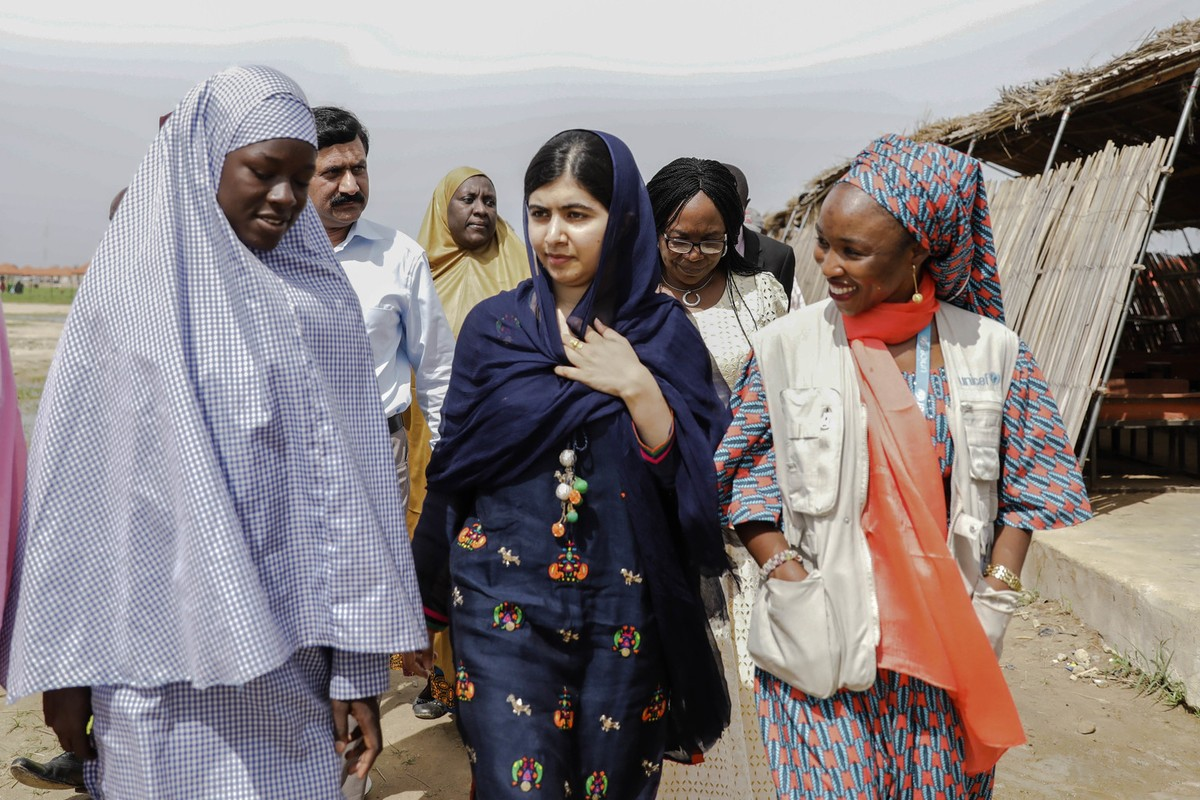 On 18 July 2017 in Maiduguri, Malala Yousafzai (center) is shown around the school in Bakassi camp by student, Fatima Grema (left) who has been displaced by the conflict in northeast Nigeria. During her visit to Nigeria, education activist Malala Yousafzai met with girls displaced by the Boko Haram crisis.