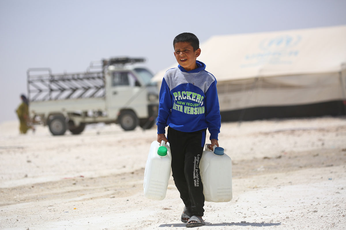 On 4 July 2017 in Ain Issa camp in the Syrian Arab Republic, a displaced boy from Raqqa carries jerrycans to fill with water.  More than 6,600 people live in harsh desert conditions, as violence continues in the area.  Since November 2016, unrelenting violence in the north eastern governorate of Raqqa has displaced over 200,000 people, almost half of whom are children. Intensified attacks have destroyed infrastructure and shattered civilian lives. Families are seeking safety in temporary shelters, with little access to basic services.  In Ain Issa camp, UNICEF has set up six child-friendly spaces for learning and playing and is providing psychological support to more than 400 children to help them cope with the traumas they have faced and to regain a sense of structure and normality.    In response to the needs of vulnerable families in the area, UNICEF is trucking in water daily to internally displaced people in camps in Raqqa and Hassakeh, including Mabrouka, Al-Hol and Ain Issa. UNICEF has installed latrines, showers and water storage tanks in the camps and is distributing family hygiene kits to protect children against waterborne diseases. Mobile health clinics have been set up to provide primary health care, including vaccinations for children and their mothers. Nutritional supplements are distributed on a regular basis.