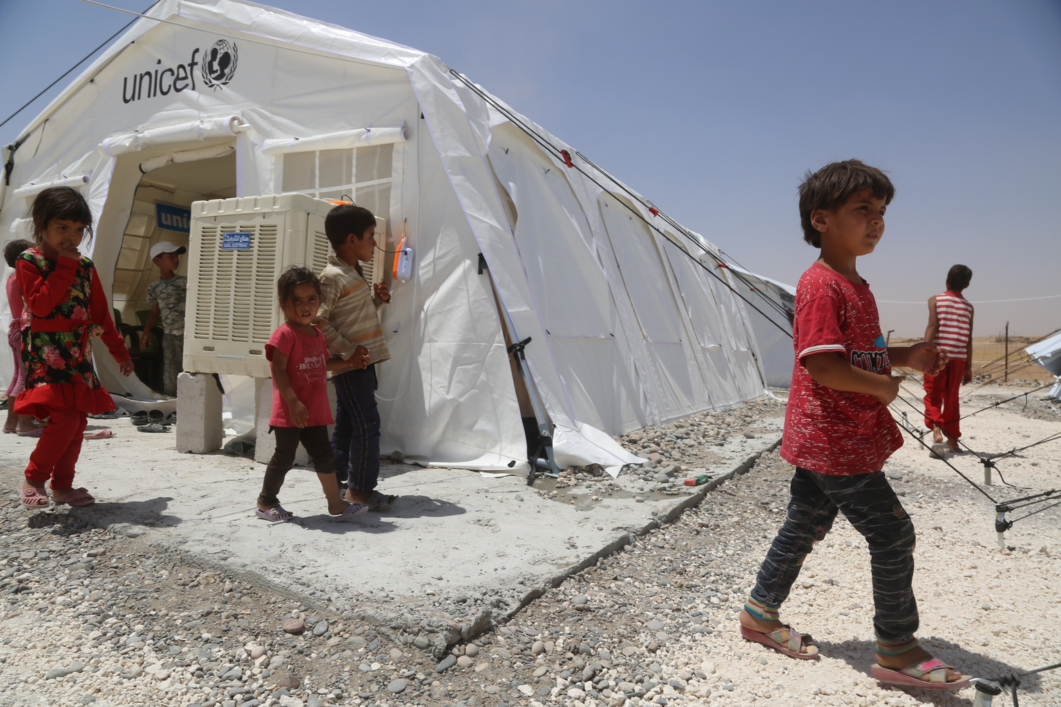 On 4 July 2017 in Ain Issa camp in the Syrian Arab Republic, displaced children from Raqqa leave a UNICEF child-friendly space which offers and a wide range of recreational activities. More than 6,600 people live in harsh desert conditions, as violence continues in the area. Since November 2016, unrelenting violence in the north eastern governorate of Raqqa has displaced over 200,000 people, almost half of whom are children. Intensified attacks have destroyed infrastructure and shattered civilian lives. Families are seeking safety in temporary shelters, with little access to basic services. In Ain Issa camp, UNICEF has set up six child-friendly spaces for learning and playing and is providing psychological support to more than 400 children to help them cope with the traumas they have faced and to regain a sense of structure and normality. In response to the needs of vulnerable families in the area, UNICEF is trucking in water daily to internally displaced people in camps in Raqqa and Hassakeh, including Mabrouka, Al-Hol and Ain Issa. UNICEF has installed latrines, showers and water storage tanks in the camps and is distributing family hygiene kits to protect children against waterborne diseases. Mobile health clinics have been set up to provide primary health care, including vaccinations for children and their mothers. Nutritional supplements are distributed on a regular basis.