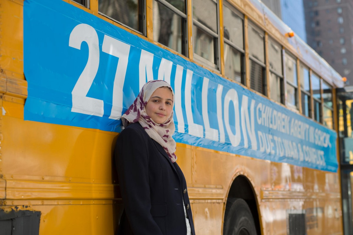 "On 17 September 2017, UNICEF Goodwill Ambassador Muzoon Almellehan stands for a portrait near a bus in the convoy of 27 empty school buses travels through the streets of Manhattan to shine a spotlight on the 27 million out-of-school children living in conflict zones. UNICEF Goodwill Ambassador Muzoon Almellehan – who was forced to give up her education as their family fled unspeakable violence in Syria in 2013 – came together ahead of the United Nations General Assembly to call on world leaders to prioritize education for every child uprooted by war, violence and poverty. The buses travelled from Brooklyn through lower Manhattan to Times Square carrying powerful messages including ""School zones shouldn't be war zones""; ""Tonight's homework shouldn't include hiding,"" and ""Avoiding landmines shouldn't be an extracurricular activity.""  A staggering 27 million children aged between 6 and 15 years old are currently being denied their right to education due to conflicts not of their making.  Funding shortfalls for education in emergencies are affecting children's access to school in conflict and natural disasters. Six-months into 2017, UNICEF had only received 12 per cent of the funding required to provide education for children caught up in crises.  UNICEF partnered with creative agency KBS and media and production partner PCI to create the live experience in New York City coinciding with the annual UN General Assembly."
