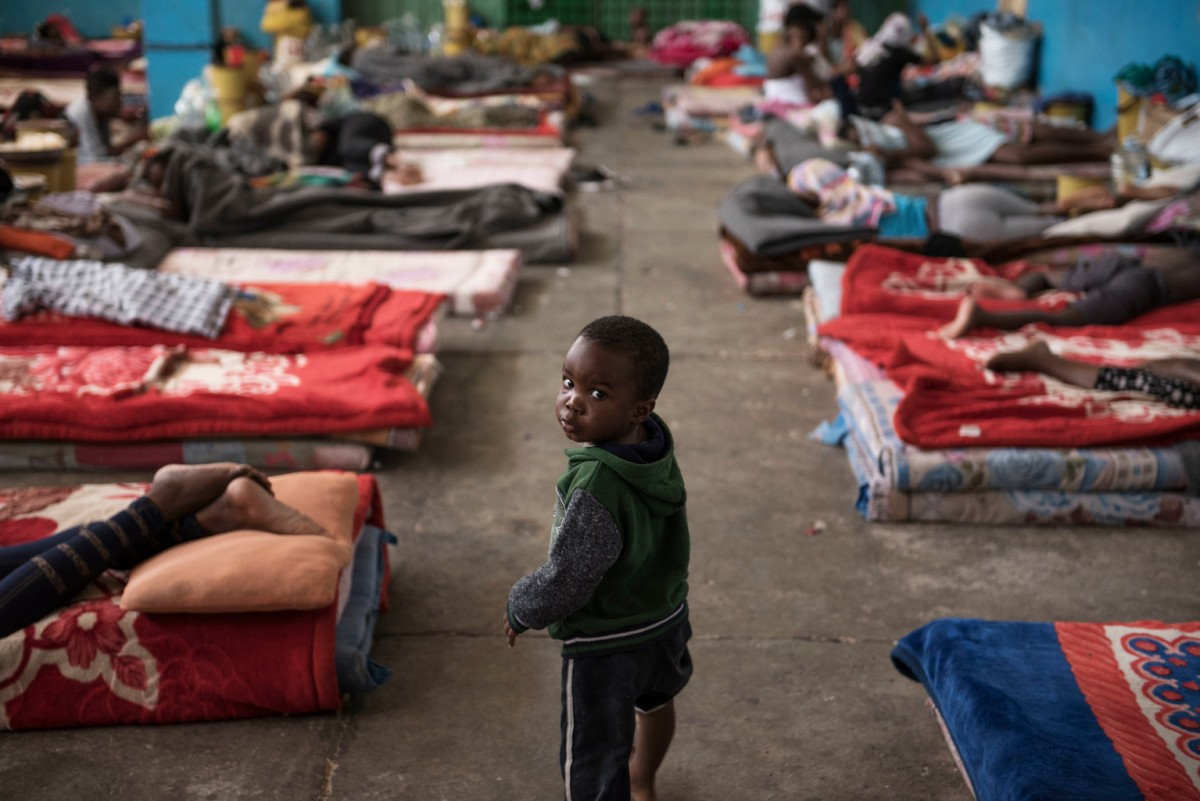 A child walks past mattresses laid on the floor in the women's section of the Al-Nasr detention centre in Zawiya, Libya, Sunday 20 August 2017.