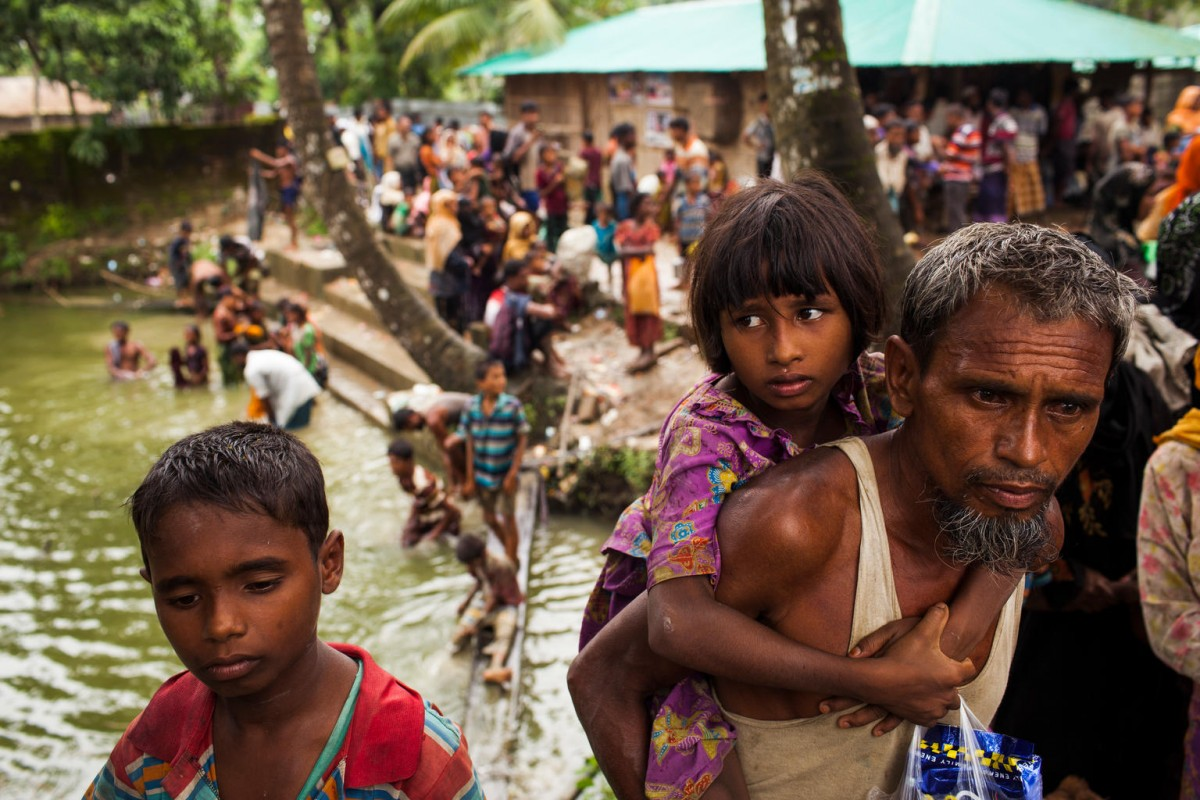 On 6 September 2017, (foreground) a Rohingya family from Myanmar who had crossed the border into Bangladesh are waiting to be transported to the nearby Balukhali makeshift settlement for Rohingya refugees in Cox's Bazar District, Bangladesh.