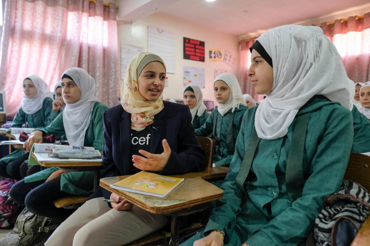 """On 15 October 2017 in Amman, Jordan, UNICEF Goodwill Ambassador Muzoon Almellehan met Grade 9 Syrian girls at the Sai'ed Noureddin double shifted public school in Amman. There are over 800 Syrian students in the school and is one of the public schools in Jordan that operates in two shifts to accommodate Syrian children. """"Returning to Jordan to meet children whose hope has been restored through education has compelled me to raise my voice even louder for the 27 million children who remain out of school because of conflict. I recommit myself to represent all of the children whose voices have been silenced for too long – and whose chance to learn, and of hope for a better future have been destroyed by war,"""" said Muzoon. The Ministry of Education, with support from UNICEF and donor countries, has opened over 200 such double shifted schools to ensure access to education for Syrian children. In addition, a catch up education programme helps children aged 9 to 12 who have missed more than 3 years of schooling to accelerate their learning and join the grade appropriate to their age.  UNICEF Goodwill Ambassador Muzoon Almellehan travelled to Jordan to meet children who, like her, fled the Syrian conflict and are now determined to go to school despite extremely challenging circumstances. It was the first time Muzoon had returned to the country – where she spent three years in refugee camps, before being resettled in the United Kingdom with her family in 2015. """"Returning to Jordan to meet children whose hope has been restored through education has compelled me to raise my voice even louder for the 27 million children who remain out of school because of conflict. I recommit myself to represent all of the children whose voices have been silenced for too long – and whose chance to learn, and of hope for a better future have been destroyed by war,"""" said Muzoon. Around 2.4 million Syrian children are missing out on education, including 1.7 million inside the Syrian"""