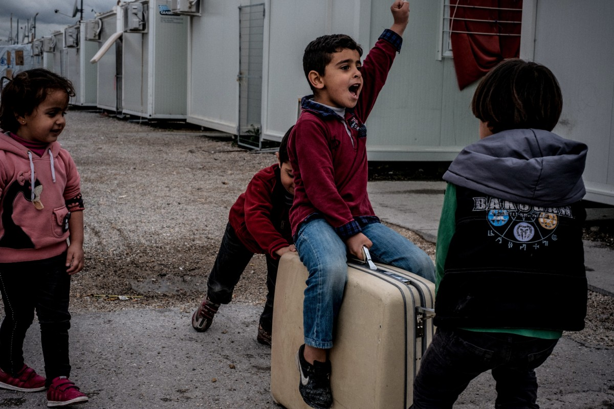 Seven-year old Louay (sitting on suitcase), six-year old Ayman (right), six-year old Manena (left) and six-year old Wael (second left) play with a suitcase that they found in the garbage at the Skaramagas refugee camp, in the port area of northern Athens, Greece, Thursday 9 March 2017. Skaramangas is the largest camp in Greece, housing over 3,000 people, and is regarded as having the best administration and facilities. On a visit after a heavy rain, open sewage pooled in large puddles between container houses, and children played with homemade toys they had found in the garbage. More than 60,000 refugees are trapped in limbo in Greece after central European countries attempted to stop the influx of refugees reaching Europe by sea during 2015 and 2016.  As of March 2017, one year after the closure of the Western Balkans migration route, irregular movements within Europe continue, but refugee and migrant children, whether alone or with family members, are increasingly facing higher fences, stricter border control and regular push-backs. Most recent concerns have been raised around new legislation in Hungary, prescribing for detention of asylum-seeking children above 14 years of age for migration control purposes.  UNICEF continues supporting child protection services in 11 Child and Family Support Hubs (Blue Dots) in open reception facilities on the mainland and in urban sites in Athens, Thessaloniki and Ioannina. Since the beginning of 2017, 1,341 children (including 507 newly registered in February) benefitted from services on regular basis.   Vulnerable refugee and migrant families and children continued benefitting from specialised psychological and mental health services in Athens and five open sites in Attica region (Elefsina, Elliniko, Agios Andreas/NeaMakri, Rafina and Elaionas).   UNICEF's ongoing partnership with the Office of the Greek Ombudsperson for Children on child rights monitoring continued in February, including organizing visits to Skaramangas