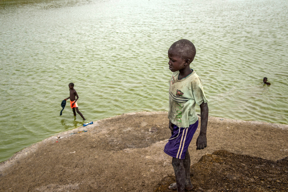 Children bathe in a lake formed by excavation pits in the Protection of Civilians site in Bentiu, South Sudan, Friday 28 April 2017. Some children have drowned swimming in these lakes. Nationwide, only 41% of children have access to safe, clean water.  More than 1.97 million South Sudanese are internally displaced since 15 December 2013, according to UNOCHA figures from May 2017. In South Sudan's Bentiu Protection of Civilians (PoC) site, the number of internally displaced persons (IDPs) seeking shelter continues to increase due to the ongoing food shortage in Unity State, with a head count in May 2017 of 121,267 IDPs. The average water supply is currently at 12.1 litres per person per day, meeting the 7 to 15 litres per person per day Sphere standards. UNICEF continues to expand the Rubkona Surface Water System, which is currently producing 340,000 litres of safe treated water per day, serving over 25,000 individuals in Rubkona town.