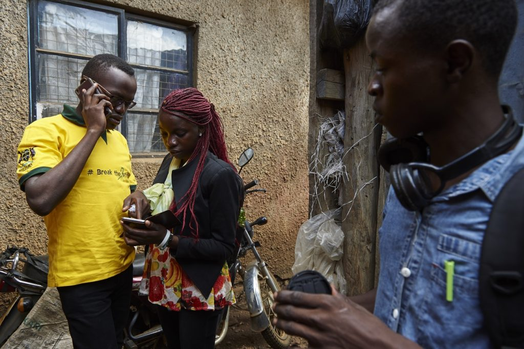 Standing in open, Collins Odour (left), Laura Adema (middle) and Dawwing Ouma (right), all of them Sauti Skika peers and advocates, communicate with their friends on phone in Nyalenda neighbourhood in the city of Kisumu. Kenya. Sauti Skika is an initiative for and by young people living with HIV, with a goal to ensure the voices of young people and adolescents living with HIV is heard at all levels of HIV response. It aims to empower adolescents living with HIV (ALHIV) to increase participation in advocacy for improved access to HIV prevention and treatment interventions, as well as for access to sexual reproductive health options and improve their quality of life. Sauti Sauti Skika seeks to have a pool of skilled and confident 'Sauti Skika' champions' as agents for change who can engage in media related advocacy. Note: When given choice, Dawwing Ouma (grey shirt), Collins Odour (yellow shirt) and Laura Adema (black jacket) from Sauti Skika insisted that they are do not want their identities to be hidden in any way as they are advocates for people living with HIV. In Kenya, over half (51%) of new HIV infections are among adolescents and young people aged 15 to 24, at an estimated 49 new HIV infections every day among 15-19 year olds. Sauti Skika is an initiative supported by UNICEF, for and by young people living with HIV, with a goal to ensure the voice of young people and adolescents living with HIV is heard at all levels of HIV response. It aims to empower adolescents living with HIV (ALHIV) to increase participation in advocacy for improved access to HIV prevention and treatment interventions, as well as for access to sexual reproductive health options and improve their quality of life.