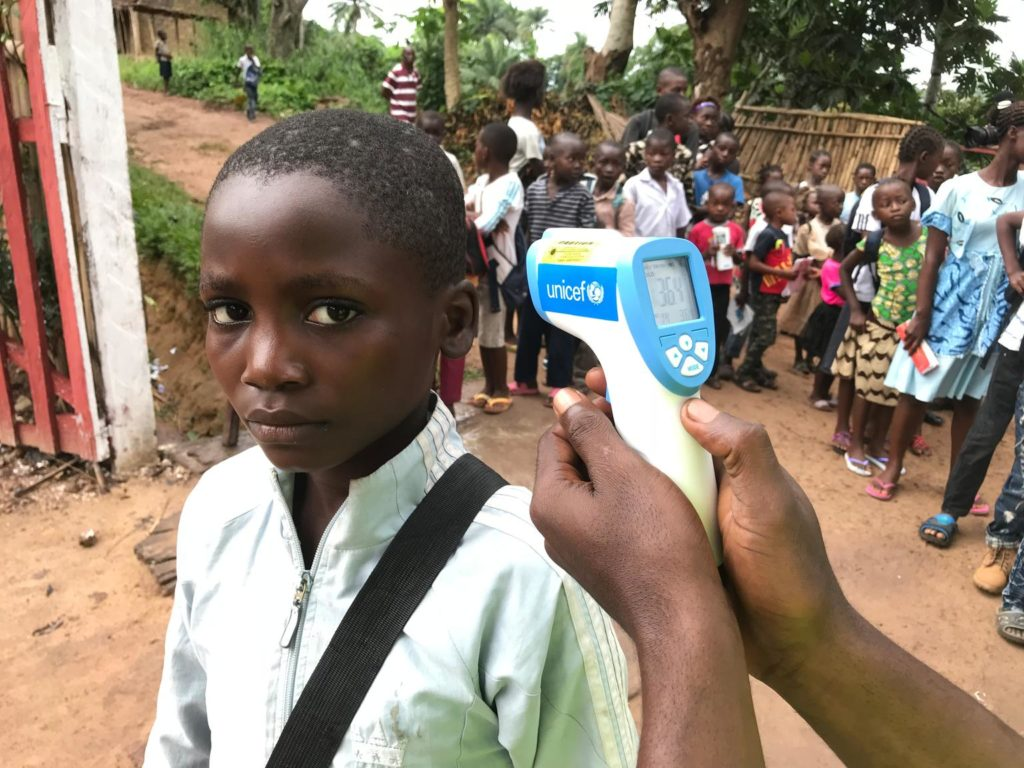 "© UN0216104/Shadid On 30 May 2018 in the Democratic Republic of the Congo, students attending primary School ""Vie Nouvelle"" in Wangata neighbourhood must wash their hands and then have their temperature screened with a UNICEF-provided infrared thermometer before entering the school, in order to reduce the risk of Ebola Virus Disease (EVD) transmission in Mbandaka, the capital of Equateur Province. Since the start of the EVD outbreak in the country, UNICEF and its partners have reached more than 300,000 people with lifesaving information about how to avoid contracting the deadline virus."