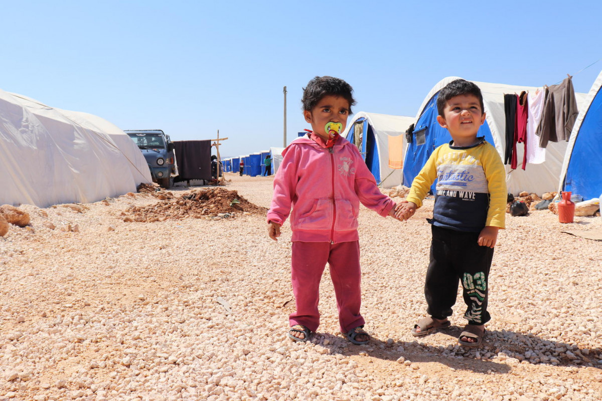 "On 25 April 2018 in the Syrian Arab Republic, children from the Fafin makeshift camp for families displaced from Afrin district. Approximately 4,000 families have settled in a makeshift camp for internally displaced people from Afrin.  In April 2018 in the Syrian Arab Republic, more than 137,000 people from Afrin district have been displaced by escalating violence since 20 January 2018. Many remain displaced after several months, mainly in Tall Refaat, Nubul, Zahra and surrounding villages north of Aleppo city. Many have left most belongings behind. Once well-off families are now sheltering in industrial halls, warehouses and mosques ill-equipped to host large numbers of displaced families. Many families with newborn babies have missed out on vaccinations because of the displacement. ""Most people forgot about vaccines at that time."" says Hajer, a health worker formerly based in Afrin and now working with the health teams in Fafin camp. In Kafr Naya, northern Aleppo, some 300 people displaced from Afrin are sheltering in the Kafr Naya School. In Zeyarah village, also in northern Aleppo, another school is now sheltering around 300 children displaced from Afrin and their families. Around 17 schools in northern rural Aleppo being used as collective shelters. UNICEF, with funding from the Global Alliance for Vaccines and Immunization (GAVI), is ensuring that all children displaced from Afrin are protected from preventable diseases and provided with a chance to catch up on their vaccinations. With funding from the European Union (ECHO) and in partnership with UNFPA and the Monastery Saint James the Mutilated, mobile clinics and health workers are providing displaced children and their mothers with primary health care services and lifesaving preventive and curative nutritional interventions."