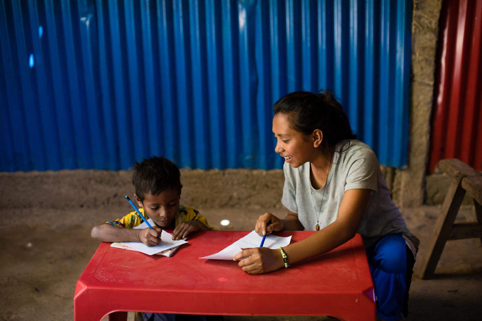 Cidalia M.E da Costa (16) , help her younger brother Januario Viegas da Costa (6) learning at home, in Aileu, Timor-Leste.