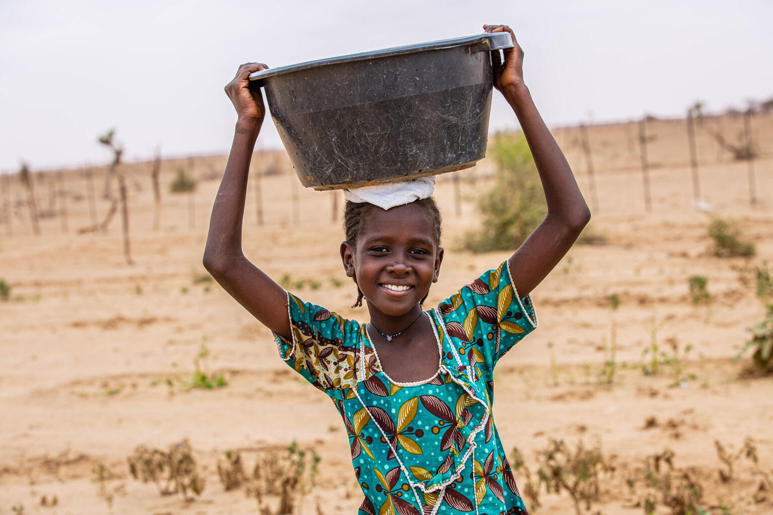 Because of the lack of water in her village, a young girl have to fetch water from huge wells dug in the ground. In the heat of the day, she carries 10 to 30 liter basins on their heads to irrigate the market garden. The operation is repeated up to 10 times a day.