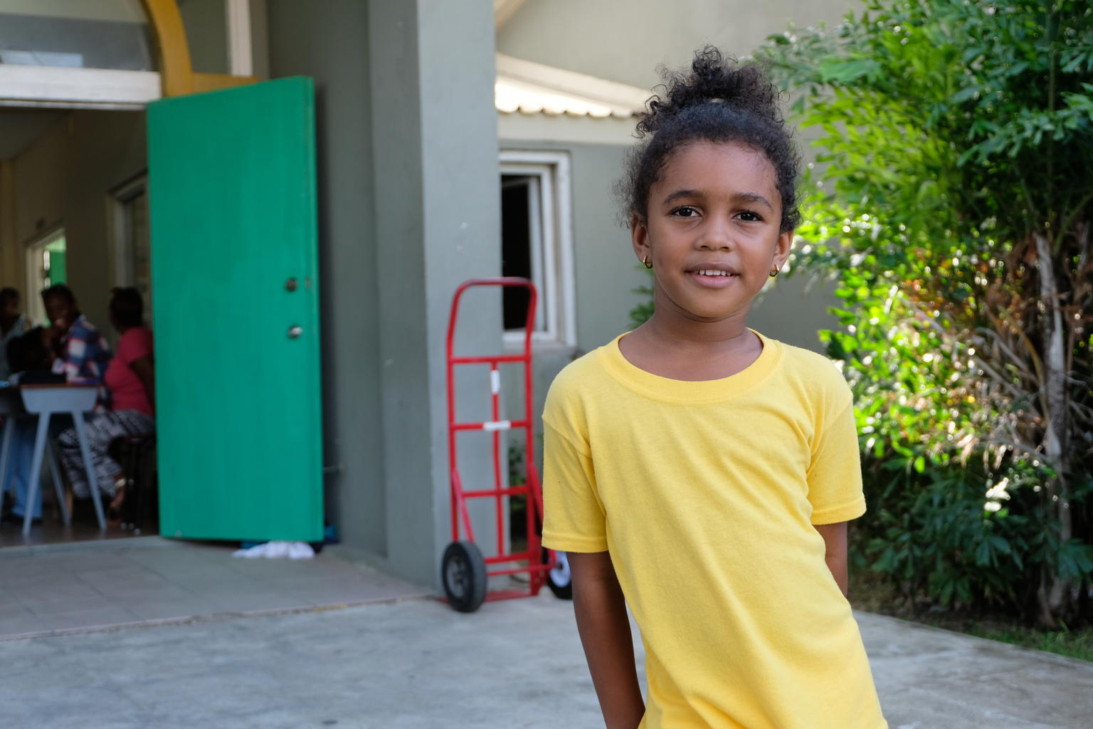 """On 10 September, 6-year-old Bella Rian Jackson smiles outside the National Technical Training Centre in St. John's, capital of the island of Antigua. The education facility currently shelters displaced families from Barbuda whose homes were destroyed by Hurricane Irma. Bella, from Antigua, volunteers at the shelter with her grandparents, sorting and folding donated clothes, cleaning and tidying up the communal areas, and helping to distribute food and supplies. """"I wanted to volunteer with my grandma,"""" Bella says. """"If the children can't come here, they'd [sic] have nowhere to go, and another storm could come,"""" she adds. More than 130 people, including scores of children, sheltered at the centre when the facility was at its busiest. On 6 September 2017, Hurricane Irma, the strongest hurricane ever recorded in the Atlantic, pummelled islands in the Eastern Caribbean. The category 5 storm left a path of destruction – especially on Anguilla, the British Virgin Islands, Barbuda and Turks and Caicos Islands. Some 73,000 people in this area, including 20,000 children, are affected, and at least 132 schools have been damaged. Irma disrupted communication networks in many areas and damaged or destroyed infrastructure, including roads, bridges, hospitals and schools. The island of Barbuda suffered extensive damage during the disaster. Over 90 per cent of its buildings were destroyed, with homes, schools, the island's only hospital, and other infrastructure destroyed or severely damaged. A 2-year-old boy was also killed during the storm, and most of Barbuda's nearly 2,000 residents have been displaced. Officials quickly evacuated the vast majority of the population to Antigua, Barbuda's sister island, ahead of an anticipated category four hurricane (Hurricane Jose) expected to wreak additional destruction on the already devastated island. Antiguans have rallied to support their compatriots, with church and community groups volunteering at shelters hosting"""