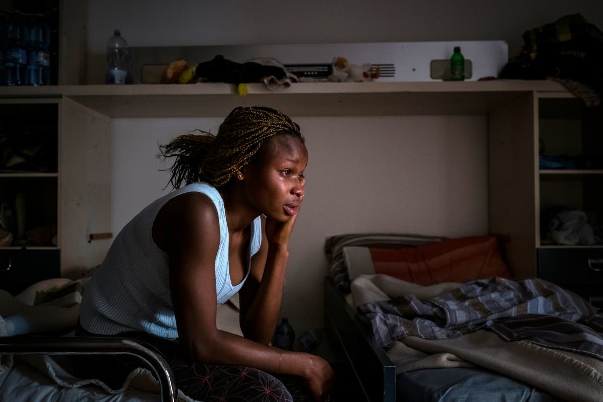 "On 27 April 2017 in Italy, [NAME CHANGED] Mary, 18, from Benin City in Nigeria, cries on a dormitory bed in the safe house where she now lives, on the outskirts of Taormina in Sicily. The safe house, run by the Penelope Association, provides shelter for women and girls who were trafficked for sexual purposes. Mary left home at the age of 17 to work in Italy, to escape a life with no prospects but was tricked by traffickers into prostitution. She was raped by a trafficker during her journey and, on reaching Italy, confessed to the authorities that knew she was going to be used in the sex trade, giving them the opportunity to remove her from the prostitution ring.  	""There is no hope in Nigeria,"" Mary said, ""I suffered a lot there, I don't have anyone to help me. I couldn't go to school. My father is dead to me, I have no siblings, so I had to work as a house girl looking after a woman's babies and cleaning her house. I was so frustrated and didn't know what to do, and my friend said I should go to Europe. I don't have anyone to rely on in Nigeria, and I decided to go. 	""Though my country is sweet and I love it, I suffered too much. There was no future there for me. A woman said she would help me and send me to Europe and she introduced me to a man, his name is Ben, who she said could help me. Ben said he knew people who had restaurants to put me to work in. For the moment, he said he would pay my expenses.  	""The next day, the man called me to his house."" Mary says. ""There were lots of boys and girls there. He said to all of us, if we made it to Europe, we all had to each pay €25,000. Some people said no, but I said that was okay."" 	""Then he took us to a place they do juju."" 	""We had to swear to an old woman –a sorcerer– that we wouldn't run."" Mary explains. 	""So, on March 17, I left for Libya. That place is very, very bad. They treated us so bad –everything Ben –, the man who took us, said – that we would be treated"