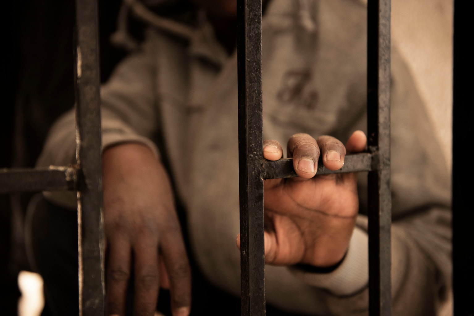 "Fourteen-year-old Issaa, a migrant from Niger, rests his hand on a gate inside a detention centre, in Libya, Saturday 28 January 2017. Issaa, who has five younger brothers, said his mother died two years ago in Niger. ""I left Niger two and a half years ago"", he says sitting on one of the dozens of dirty mattresses on the floor. ""My father collected money for my journey, he wished me good luck and then let me go. Once I arrived in Libya I started to look for a job."" When Issaa was 12 years old, he began to work on a farm. He worked for less than thirty dollars a month, taking care of the farm and feeding the animals. He managed to set aside US$450, which he hoped would pay for a crossing by boat to Italy. He was arrested and detained before he was able to board a boat. At the time of UNICEF's visit to the detention centre there were ten women, three children and 51 men being held. Issa was the youngest unaccompanied minor in detention. The men's and women's areas are on the same floor, divided only by a locked gate with a padlock. The women being detained were all arrested in Sirte during a recent military offensive. As such they were being detained ""pending interrogation"" and were not classified as illegal migrants. Libya is a country in turmoil. Since 2014 security is precarious, living is hard, and violence is commonplace. The country is riven with militias in conflict with each other or Government forces. Thousands of children and women hoping to reach Europe travel from Africa and the Middle East to the sea in Libya. They endure exploitation, abuse, violence and detention. In 2016, 181,000 migrants used the route to reach Italy, 25,800 were unaccompanied children. Children and women making the journey live in the shadows, unprotected, outside the law, and reliant on smugglers. Migrants are easy prey and the average number in detention is 6000-7000, depending on the season. The international community, including UNICEF, only has access to some of t"