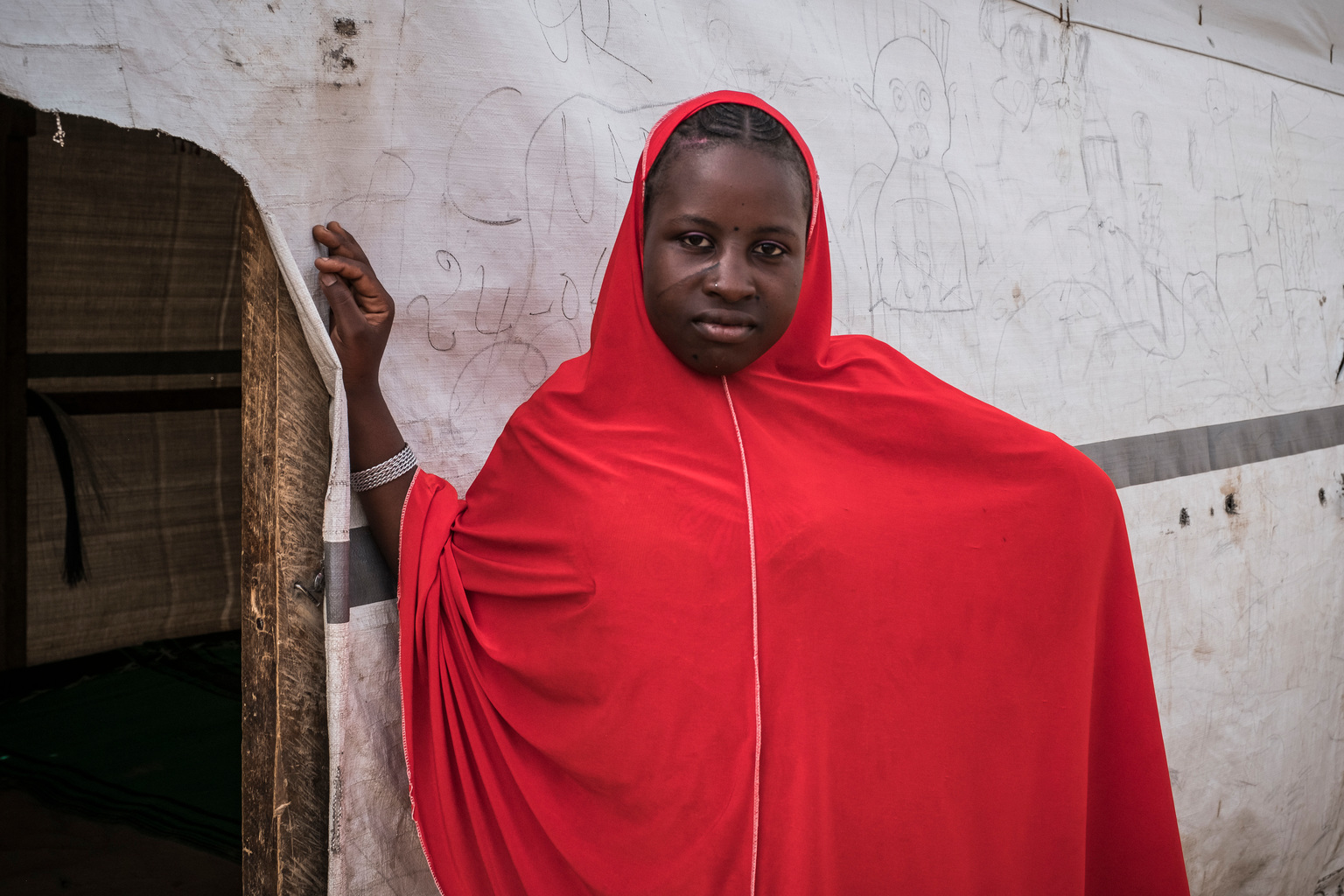 Nigerian refugee Hafsa Oumar, 16, stands outside a classroom at the Dar Naim school, in Daresalam refugee camp, Lake Region, Chad, Thursday 20 April 2017. Before coming to Chad, Hafsa never had a chance to attend school. Hafsa enrolled in school for the first time when she arrived in Chad in 2015. However, she stopped attending school following her marriage in February 2017. More than 25 million children between 6 and 15 years old, or 22 per cent of children in that age group, are missing out on school in conflict zones across 22 countries. In response to the education crisis in Chad, UNICEF has since the start of 2017 provided school supplies to more than 58,000 students, distributed teaching materials to more than 760 teachers, and built 151 classrooms, 101 temporary learning spaces, 52 latrines and 7 sports fields. UNICEF Chad also supported the salaries of 327 teachers for the 2016-2017 school year. To help drive an increased understanding of the challenges children affected and uprooted by conflict face in accessing school, UNICEF advocate Muzoon Almellehan, a 19-year-old Syrian refugee and education activist, travelled to Chad, a country where nearly three times as many girls as boys of primary-age in conflict areas are missing out on education.