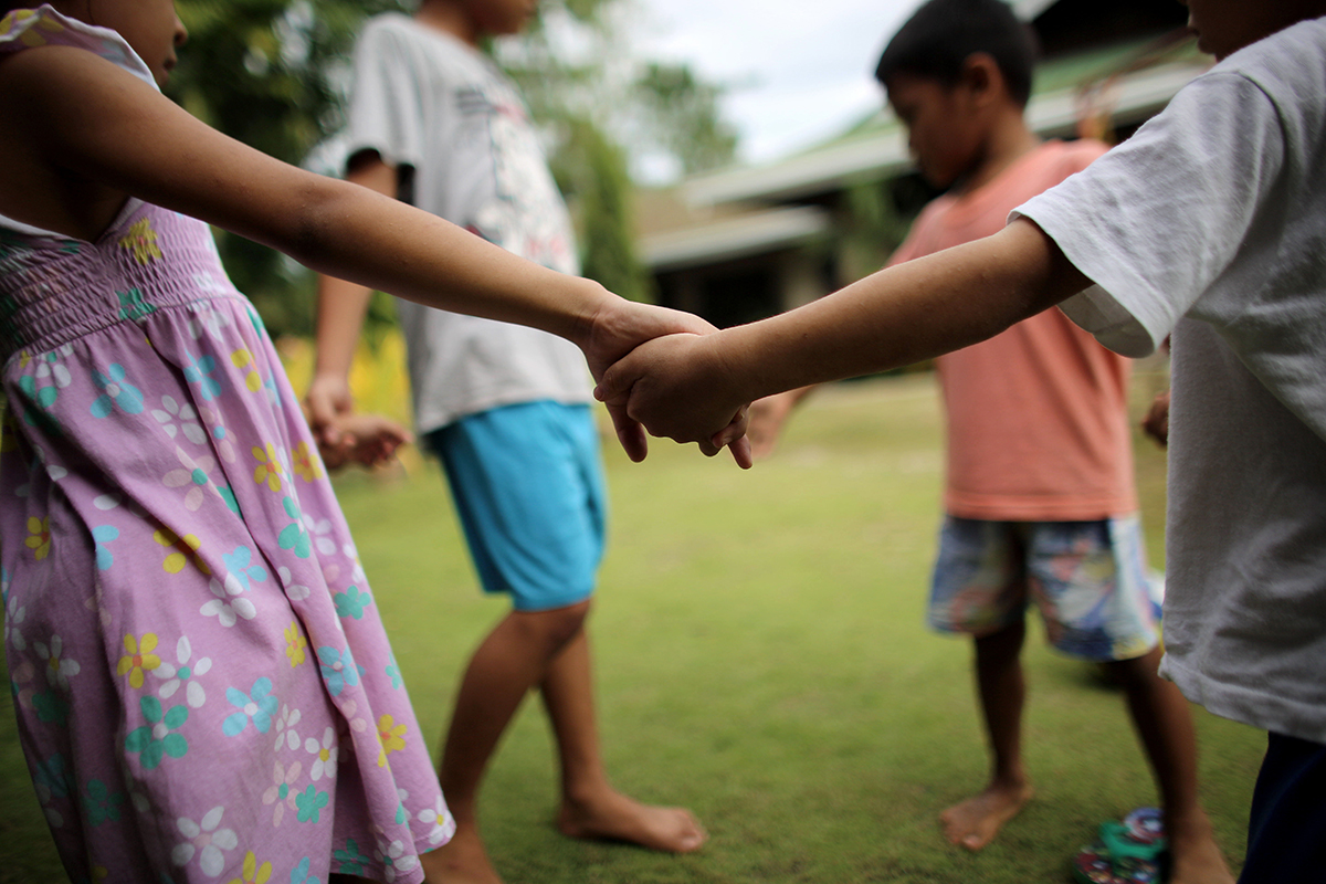 [NAME CHANGED], On 12 March 2016, a group of children play ing-round-the-rosy?outside their home at a shelter in the Philippines. Three of the children and their older sister, Rosalyn (not pictured) are among 7 siblings who were rescued during a cyber crime police raid police 6 years ago when their parents were caught forcing the two oldest girls to participate in live streaming of child sexual abuse in their home. Despite her young age, Rosalyn, now 17, has assumed the role of mother to her younger siblings at the shelter.Rosalyn remembers her childhood fondly until her parents lost their jobs at a local factory. Uneducated, they were unable to find work and the family soon sank into extreme poverty. A neighbour offered Rosalyn the opportunity to earn money by participating in live streaming of child sexual abuse. She never received money directly but noticed that her family no longer went hungry. Her younger sister began to perform online as well, and the family economic condition improved to the point that their parents were able to purchase their own computer system. The parents, under the direction of the neighbour, continued to force their two older daughters to participate in live streaming of child sexual abusein front of a webcam in their home. The parents are now in prison and the case is in court, pending a decision at the end of April. The youngest children do not remember their parents and Rosalyn feels conflicted and responsible for the destruction of her family. It took her a long time to understand that what had happened to her was buse?since the exploitation of children through the live streaming of sexual acts before a webcam has been normalized in their community. The children were placed in a shelter away from their community, where they receive counselling and support. Rosalyn and her older brother are now going to university and the younger children attend school. Rosalyn is an advocate for online safety, and speaks to fello