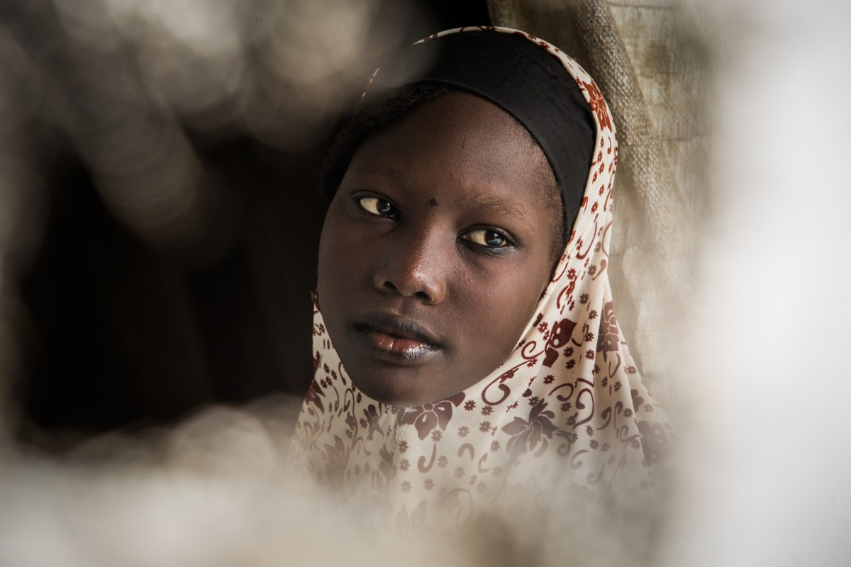 "5 August 2016 - Daresalam refugee camp, Chad's Lac Region. Portrait of Khadija Kaku, through a hole in the family shelter.  The forced journey of Khadija, a refugee in Chad Written by Badre Bahaji  Listening to the story of Khadija, 15, and her many travels, I could imagine the dangerous road that these migrant children have taken. In 5 years, ""Khadi"" as her friends call her, has lived in five different places because of conflict or drought.  Khadija Kaku lives in the Daresalam refugee camp in Chad's Lac Region. ""My father is a farmer, he left us to go to work a plot of land leased near the shores of the Lake. He doesn't want us to live on humanitarian aid alone,"" she says, proudly.  Kaku Khadija was born in Ariboye, a remote village in north-eastern Nigeria with no school and no clean drinking water. Her parents rented a small piece of land to work, but it wasn't enough. ""In 2010, there was another drought. We couldn't harvest enough to live on for the rest of the year. We had to leave our home to travel to the village of Meltri on the shores of Lake Chad. Our uncle welcomed us there,"" she continues.  The life of a teenager  Khadija's life in Meltri looks like the life of the kind of teenager I know. ""My uncle had a television, a computer and a small shop where he charged people's phones. This is where I developed a passion for new technologies. We watched Bollywood shows and music videos from all over Africa. Then we'd go out with friends and try to imitate the movies or the lyrics for fun,"" she says with an embarrassed smile.  It was also in Meltri where Khadija discovered school, quickly advancing to grade 5. Reality would soon catch up to her however. ""One morning when we entered the classroom, we found a letter slipped under the door of the school at night, written in Hausa by Boko Haram. The letter ordered parents to send their children home, and teachers to leave the area."" The tone of her voice changed immediately as she recounted the inci"