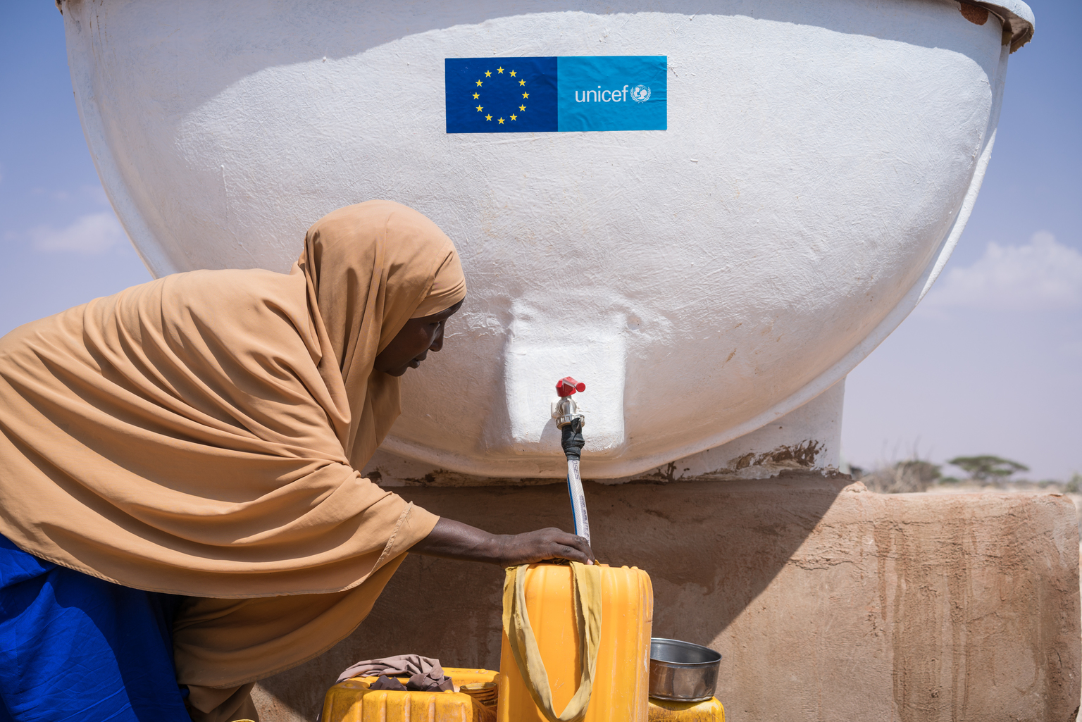 A young woman displaced from her home by the worsening drought fills containers with clean water to carry back to her new home in the internally displaced peoples camp in Galkayo, Somalia, Wednesday 12 April 2017. As of April 2017, the humanitarian situation in Somalia continues to deteriorate due to the severe drought, which started in the north in 2016 and is now affecting most of the country. Over 6.2 million people are facing acute food insecurity and 4.5 million people are estimated to be in need of water, sanitation and hygiene (WASH) assistance. The situation is especially grave for children. Close to one million children (under five) will be acutely malnourished in 2017, including 185,000 severely malnourished, which may increase to over 270,000 if famine is not averted. Severely malnourished children are nine times more likely to die of killer diseases like cholera / acute watery diarrhea and measles, which are spreading. The drought is also uprooting people, with more than 530,000 displaced since November 2016, adding to the 1.1 million already internally displaced (IDPs). This includes 278,000 new IDPs in the month of March alone, with 72,000 new arrivals in Mogadishu and 70,000 in Baidoa. In addition, the number of people crossing into Kenya is increasing. The rapid scale of displacement increases the risk of family separation and gender-based violence. Children are also dropping out of school, with 50,000 children reported to have stopped going to school, and an additional 40,000 at risk of being forced to interrupt their schooling. The Gu (April-June) rains are slowly unfolding, bringing much needed relief to parts of the country. But the rains also spell danger for children. If they come in full they will inflict further misery on children living in flimsy, makeshift shelters made of twigs and cloth or tarps. If the Gu rains fail, and if assistance doesn't reach families, more people will be forced off their land into displacement camps. Outbr