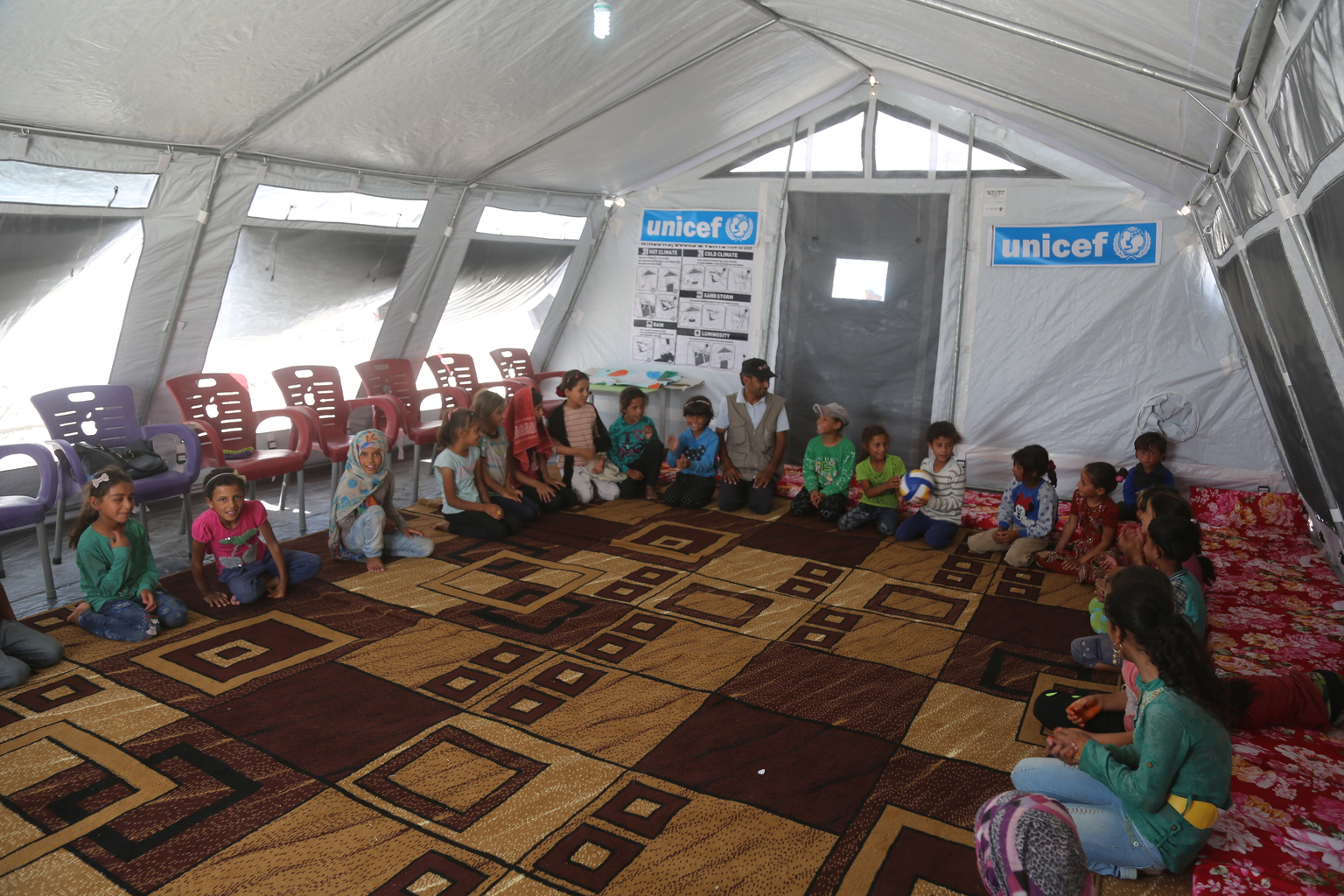 On 4 July 2017 in Ain Issa camp in the Syrian Arab Republic, displaced children from Raqqa attend a UNICEF psychosocial support programme. More than 6,600 people live in harsh desert conditions, as violence continues in the area. Since November 2016, unrelenting violence in the north eastern governorate of Raqqa has displaced over 200,000 people, almost half of whom are children. Intensified attacks have destroyed infrastructure and shattered civilian lives. Families are seeking safety in temporary shelters, with little access to basic services. In Ain Issa camp, UNICEF has set up six child-friendly spaces for learning and playing and is providing psychological support to more than 400 children to help them cope with the traumas they have faced and to regain a sense of structure and normality. In response to the needs of vulnerable families in the area, UNICEF is trucking in water daily to internally displaced people in camps in Raqqa and Hassakeh, including Mabrouka, Al-Hol and Ain Issa. UNICEF has installed latrines, showers and water storage tanks in the camps and is distributing family hygiene kits to protect children against waterborne diseases. Mobile health clinics have been set up to provide primary health care, including vaccinations for children and their mothers. Nutritional supplements are distributed on a regular basis.