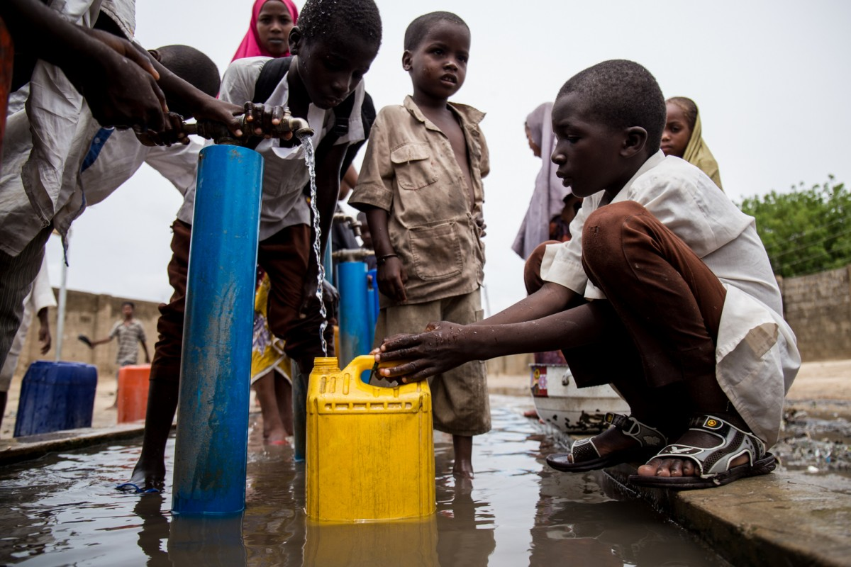 """On 13 June 2017, children collect water in Maiduguri, capital of Borno state in north-east Nigeria.  Each year, the countries around Lake Chad (Niger, Nigeria, Chad and Cameroon) suffer from severe flooding as part of the seasonal rains in the region in June 2017. Many children are at increased risk of waterborne disease as the rainy season begins in crisis-affected areas around Lake Chad. The flooding and muddy roads are expected to severely limit humanitarian access to remote areas for several weeks. This reduced access comes at a time when the needs of the population are sharply increasing with ongoing displacement and overcrowding in IDP camps. To exacerbate the risk brought by unstable weather, security concerns are significantly heightened during the month of Ramadan. There has been a sharp escalation in violence in recent weeks, including a deadly attack on Borno state capital. Security concerns are further complicating plans to preposition humanitarian supplies before the rains as the supplies could become a valuable target. UNICEF warns that there is an increased risk for children of cholera, diarrhoea and malaria. UNICEF is particularly concerned for children living in cholera """"hotspots"""" for both returnees as well as new arrivals in flood prone areas, as they are the most vulnerable and their needs must be immediately addressed."""