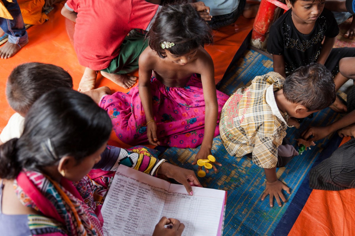 On 29 September 2017, students with their teacher going through their studies at the Child Learning Centre at the Unchiprang Makeshift Camp in Cox's Bazar district in Bangladesh.