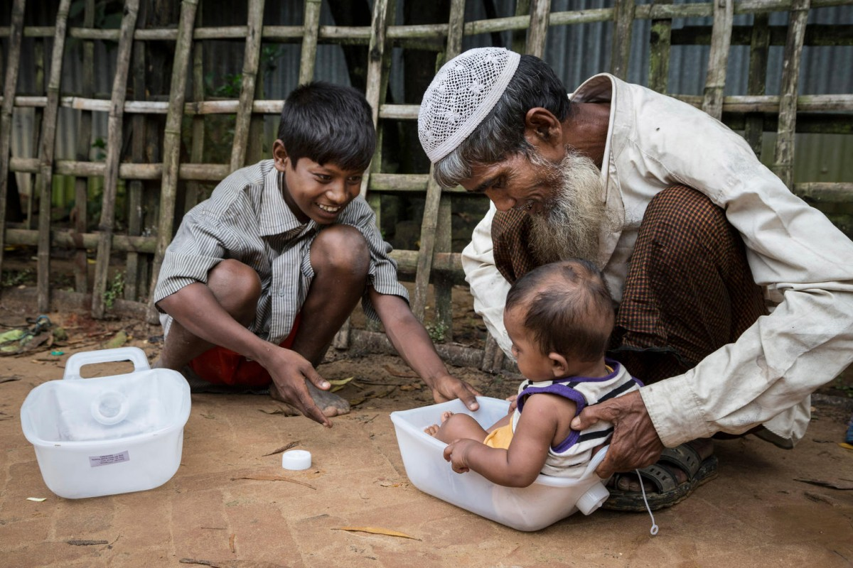 A man and boy use a plastic jerrycan as they play with a baby by sliding him around on the roadside leading into Kutupalong refugee camp in Ukhia, Cox's Bazaar, Bangladesh, Friday 20 October 2017.