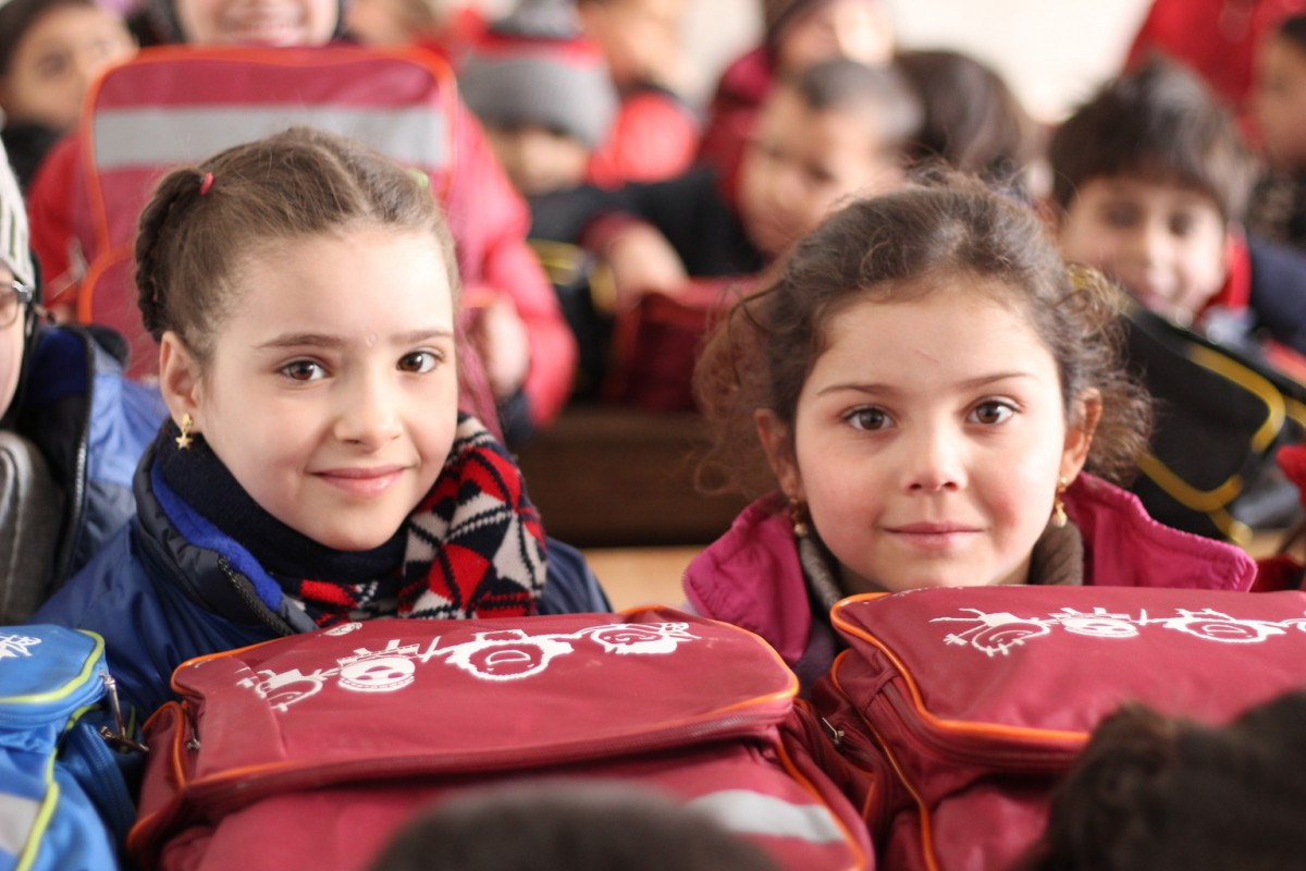 On 29 January 2017 in the Syrian Arab Republic, Rayan (left), 7, attends Grade 2 on her first day of school at the Kheir eddine Al-Asadi School in the Sakhoor neighbourhood of eastern Aleppo. The third floor of the school building sustained heavy damage during the fighting and remains unusable.  Approximately 600 children are squeezed into classrooms on the remaining two floors.  UNICEF and its partners are conducting rapid assessment of school conditions in East Aleppo.  Of the 422 schools, 217 are either destroyed, damaged or inaccessible.  As of 31 January 2017, UNICEF has supported the re-opening of 23 primary schools in the eastern parts of Aleppo city over the past weeks, allowing nearly 6,500 children to return to school.  UNICEF has provided school supplies, developed an accelerated learning programme and trained teachers to help displaced children catch up on the months and years of education they have missed. Ten prefabricated classrooms were also set up.  An urgent awareness-raising programme has been rolled out to inform children and families about the dangers of unexploded remnants of war. So far the programme has reached 50,000 children. Psychosocial support activities have been provided to 35,000 children in shelters and other locations, to help them recover from the horrors they lived through.