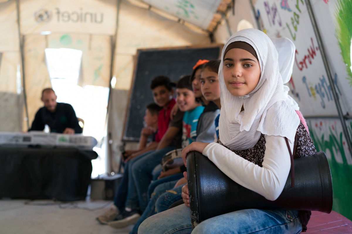 [AWAITING BRAND STRATEGY RELEASE]On 13 October 2016 at the UNICEF child friendly space, 11-year-old Fatima Al loz, a refugee from Syria, plays a traditional drum. She's seated on a bench among other young boys and girls. In the background there is a DJ. Fatima is from Homs, a city in western Syria. Her and Baba Omar are now living in Oumariyeh Informal Settlement, Bekaa, Lebanon. UNICEFÕs child friendly spaces offer a safe and creative space for children to learn and play, often within camps or settlements inhabited by Refugees and Migrants uprooted by conflict. UNICEFÕs initiatives represented here are child protection along with child survival and adolescent development, inclusion, play and out-of-school education.