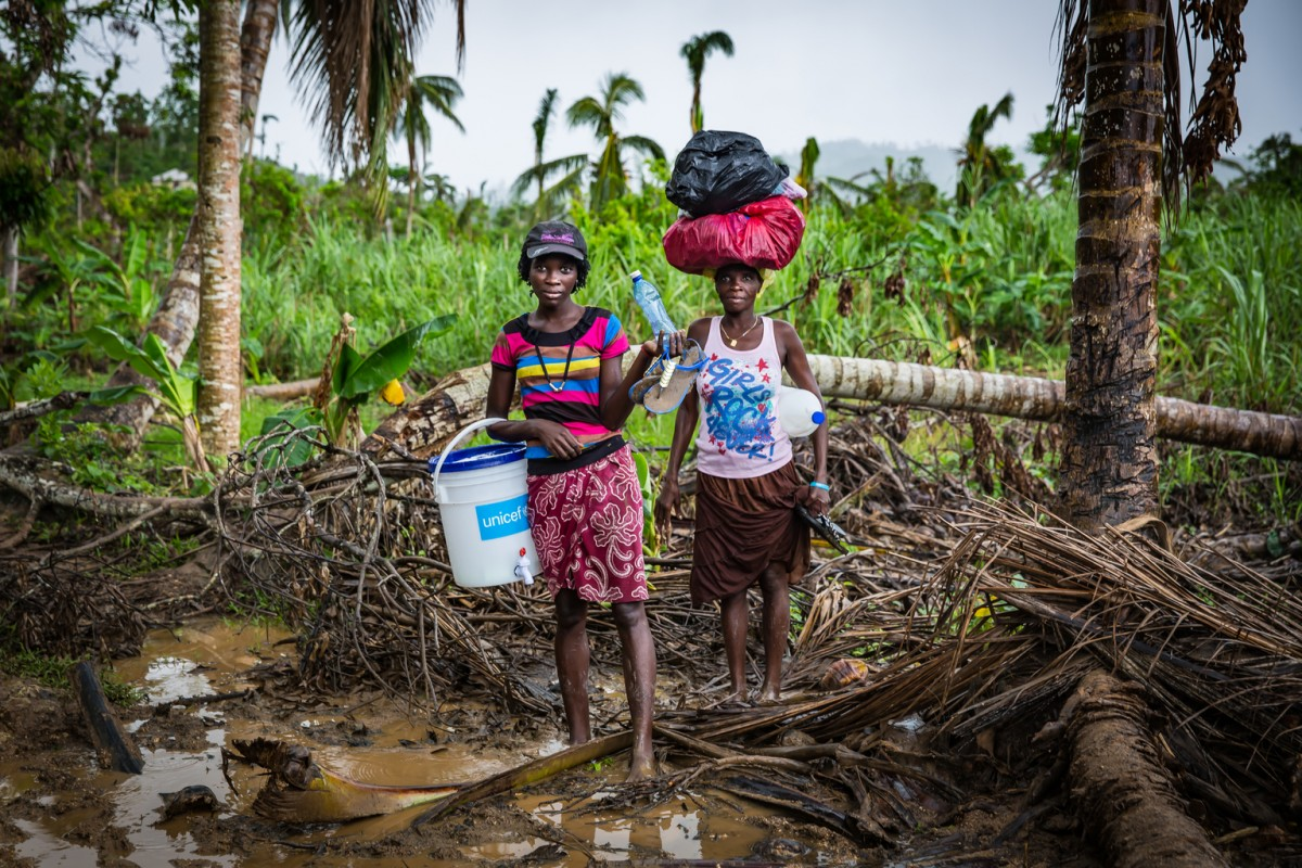 "On 8 November 2016 in Abricot, Grande Anse Department, Haiti, women carry water and supplies along routes which remain difficult to traverse.   By 4 January 2017, together with the government of Haiti, UNICEF and its partners have been able to ensure safe water is available daily to over 281,000 individuals, including over 118,000 children.  Almost three months after hurricane Matthew struck Haiti on 4 October 2016, UNICEF and its partners continue to deliver humanitarian aid to those most affected by the category 4 storm. Over 2 million people including 900,000 children were affected by the hurricane, of which 1.4 million require humanitarian assistance including 600,000 children.  In addition to the personal losses of homes and crops, over 716 schools, and many health facilities and the existing sanitation infrastructure all suffered damage.  ""Three months after Matthew, we can already see improvements: safe water is increasingly available, the vast majority of schools have reopened as have a number of health facilities; and areas that are the most difficult to access are receiving assistance. UNICEF is continuing to fulfil its mandate and obligations to emergency and development efforts,"" said UNICEF Representative in Haiti Marc Vincent.  Hurricane Matthew passed over Haiti with heavy rains and winds. While the capital Port-au-Prince was mostly spared from the hurricane's full strength. The western area of Grand'Anse, however, was in the direct path. The cities of Les Cayes and Jeremie received full force sustaining winds and water damage across wide areas. Coastal towns were severely damaged as were many homes in remote mountainous regions. An estimated 500,000 children live in the Grand'Anse and South departments, the areas worst hit by Hurricane Matthew."