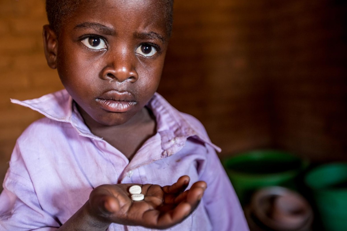 [RELEASE OBTAINED] Photographed in August, Longezo is 3 and living with HIV in Nkhuloawe Village, Malawi. Here is taking his medication. His life was saved when Bizwick, a health worker pictured right, visited his home and discovered he was very ill and in need of medical attention.  Malawi first piloted treatment for all pregnant women (Option B+) in 2011. Since then, health workers have been working tirelessly to test for HIV and prevent new infections in women and their families, and to keep those living with HIV on treatment. Here is Bizwick's amazing story.